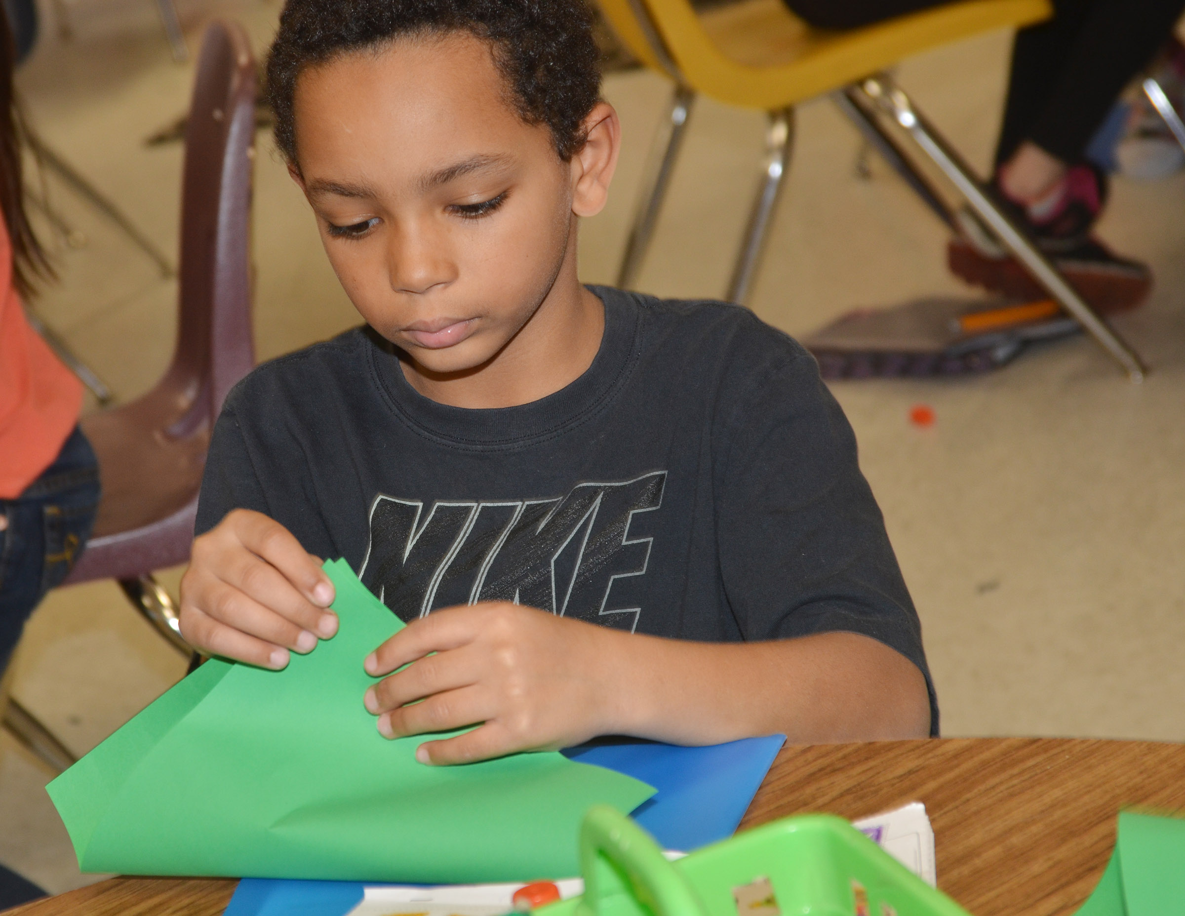 CES third-grader Jalen Embry folds his paper to make his Christmas tree.