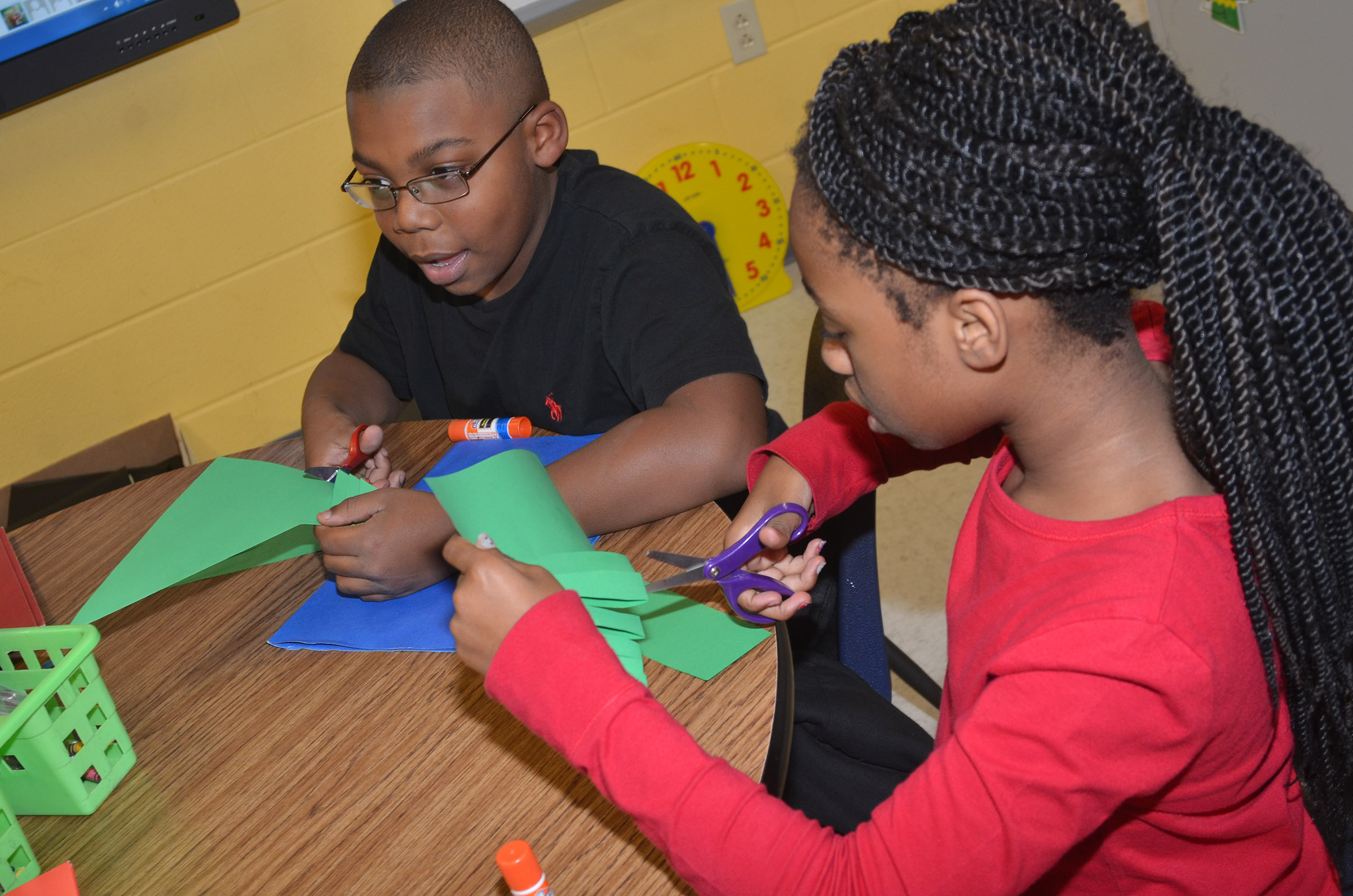 CES third-graders Austin Sloan, at left, and Tiffani Gaddie cut their paper into a Christmas tree.