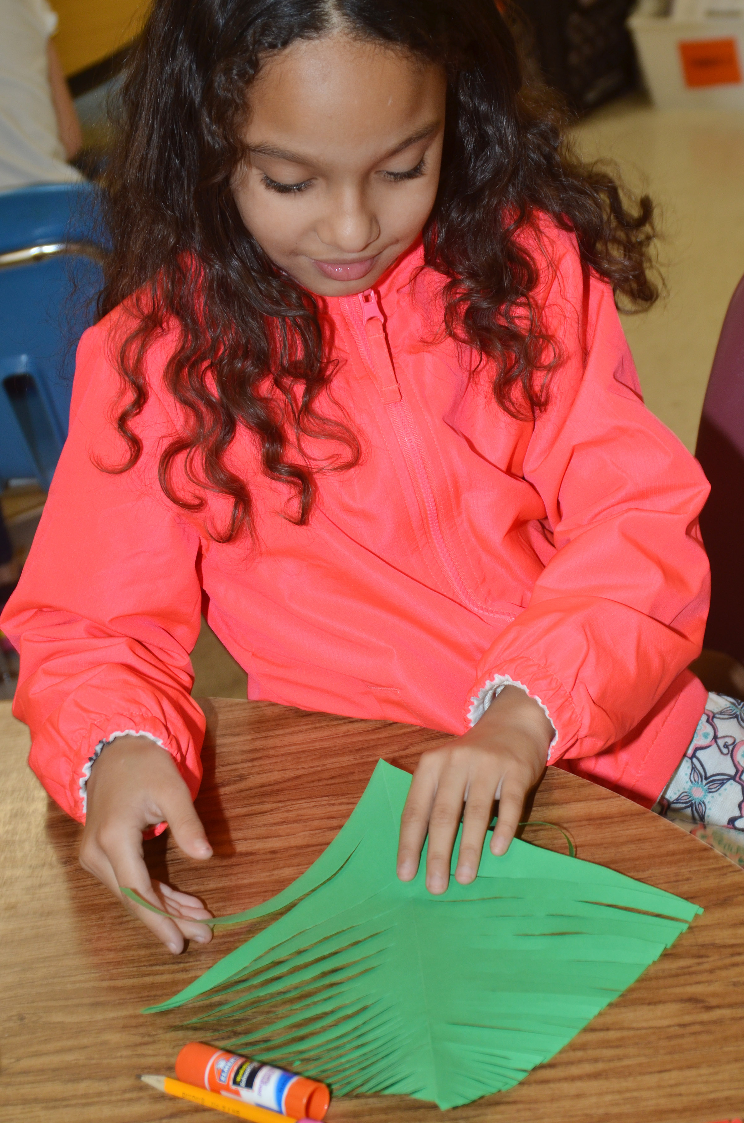 CES third-grader Alyssa Knezevic folds her paper after cutting it.