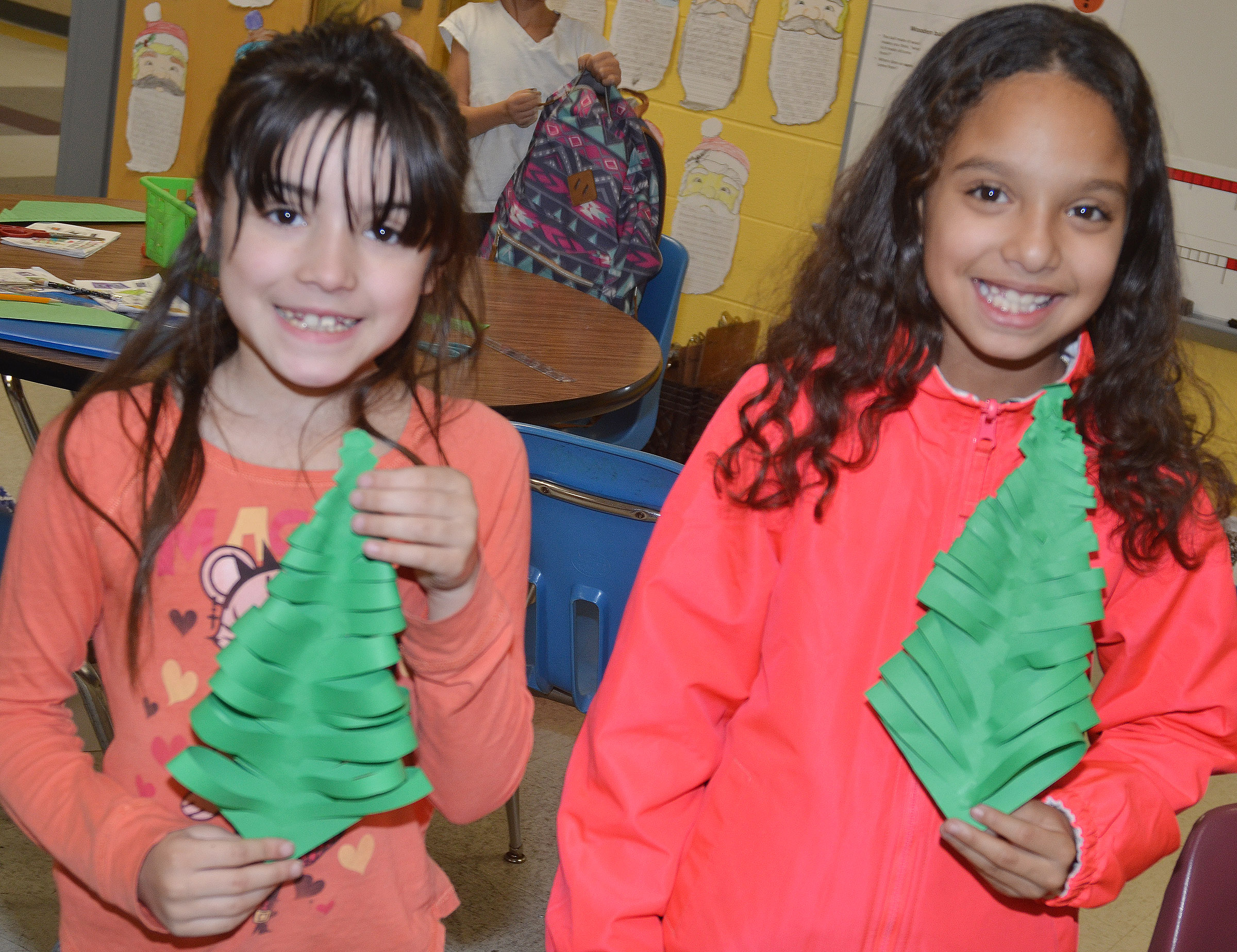 CES third-graders Zehavah Negron, at left, and Alyssa Knezevic hold their finished Christmas trees.