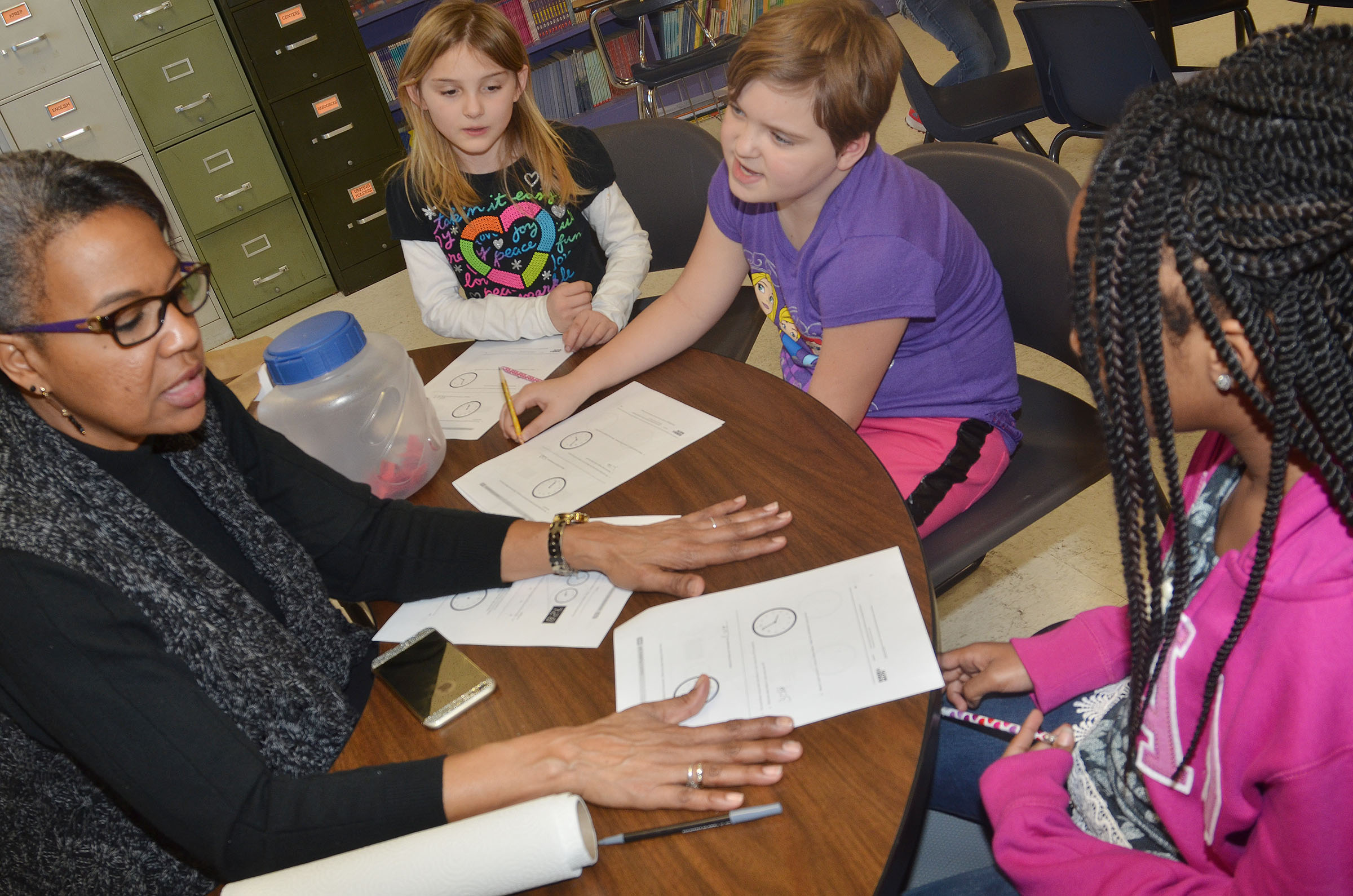 CES third-grade teacher Doretha Sanders helps, from left, Miranda Edwards, Mary James and Tiffani Gaddie practice telling time.