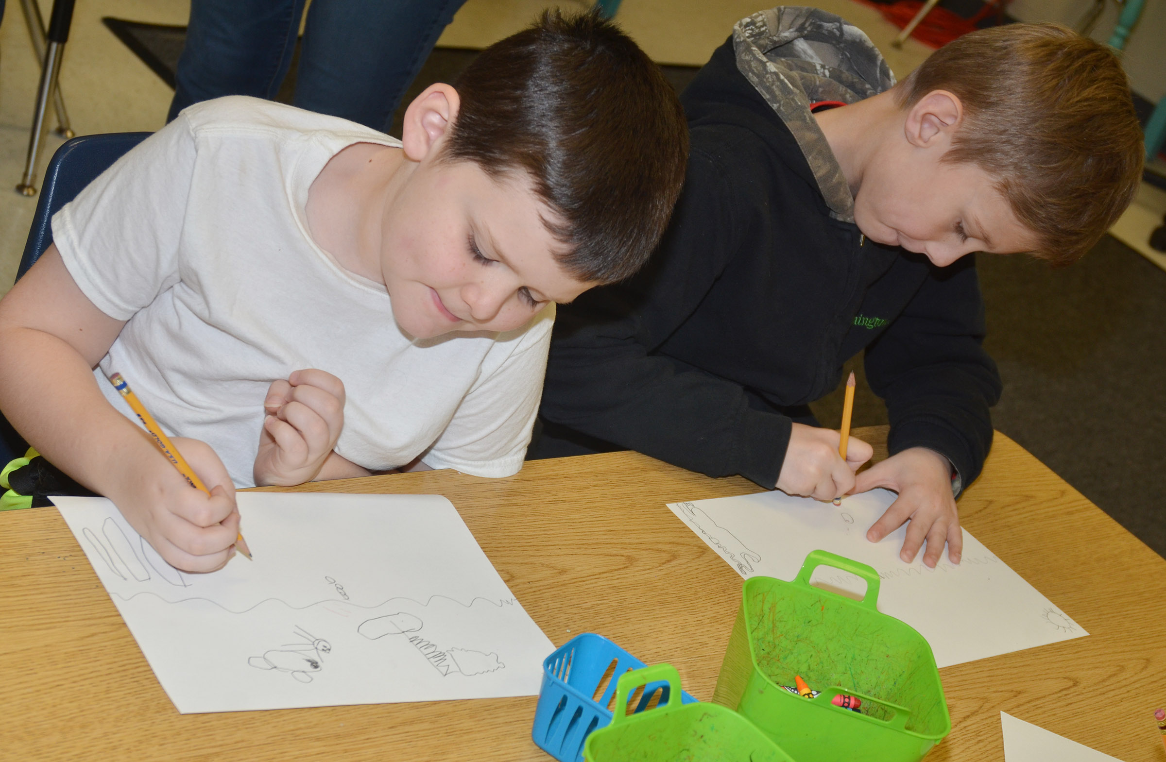 CES second-graders Weston Veltman, at left, and Isaya Adams draw their seascapes.