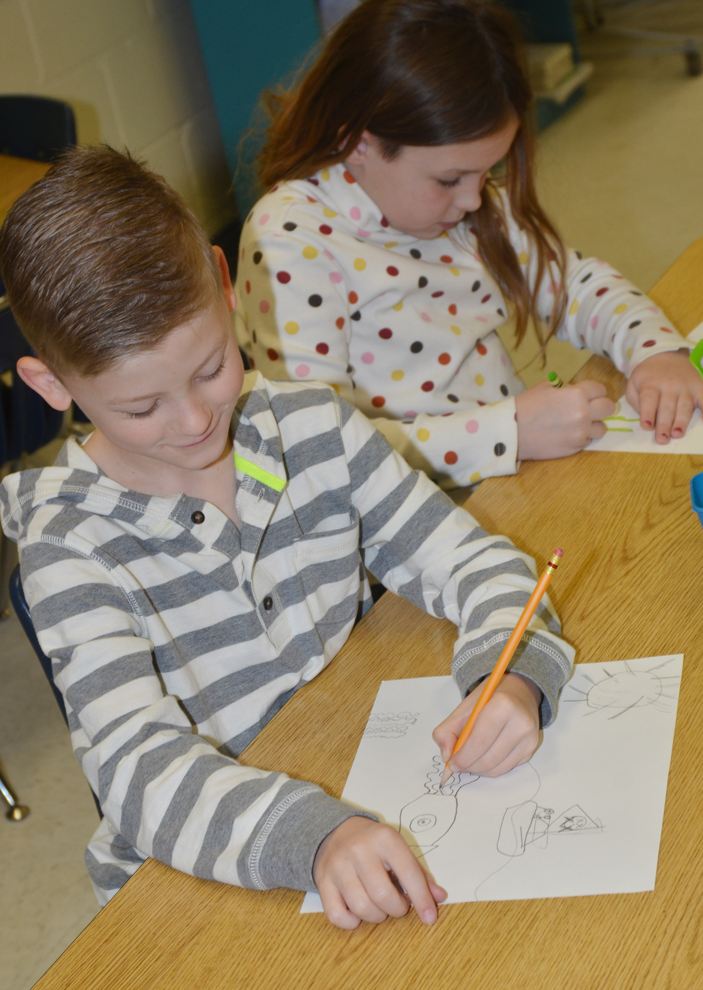 CES second-graders Malachi Sanford, at left, and Evelyn Stancill draw their seascapes.