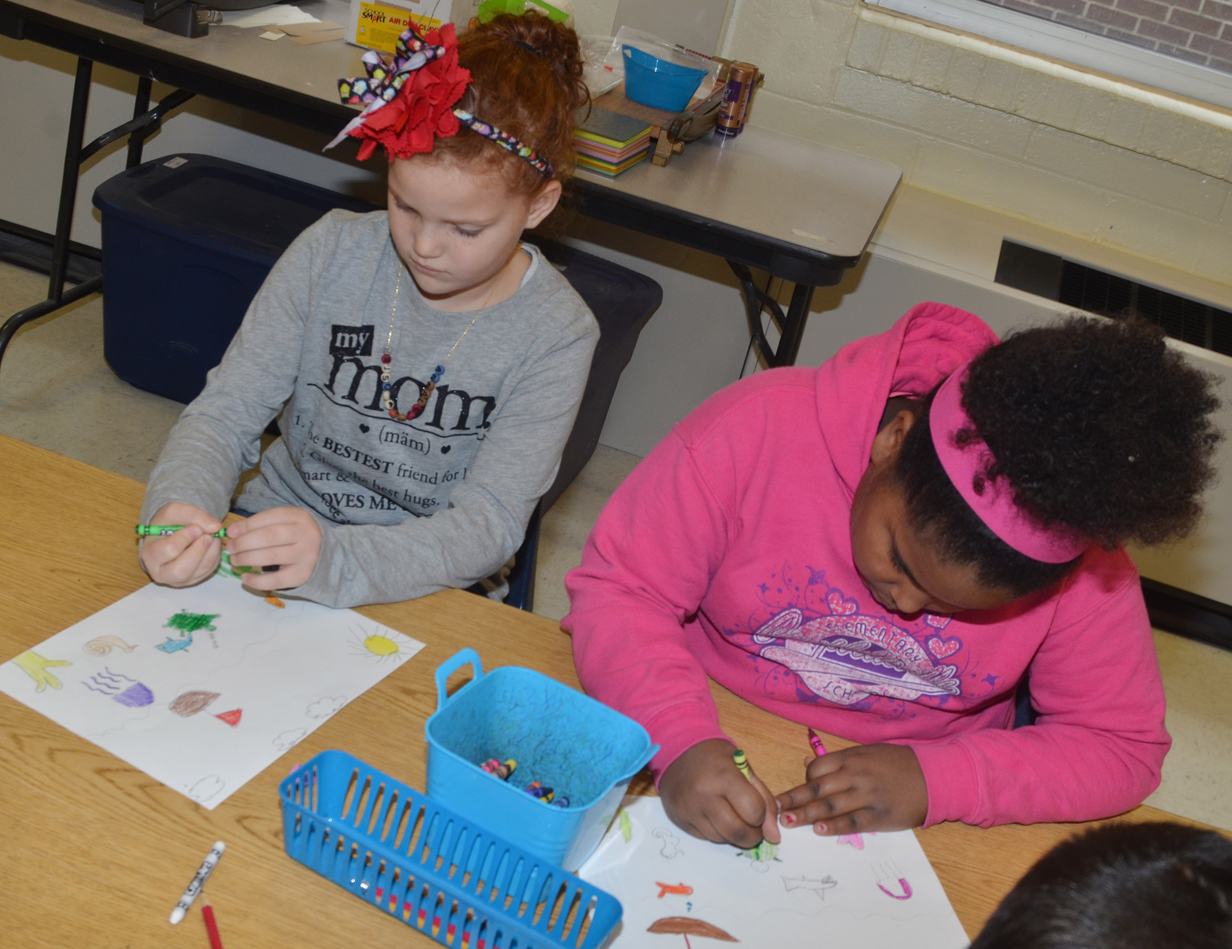 CES second-graders Analeigh Foster, at left, and Ajada Smith color their seascapes.