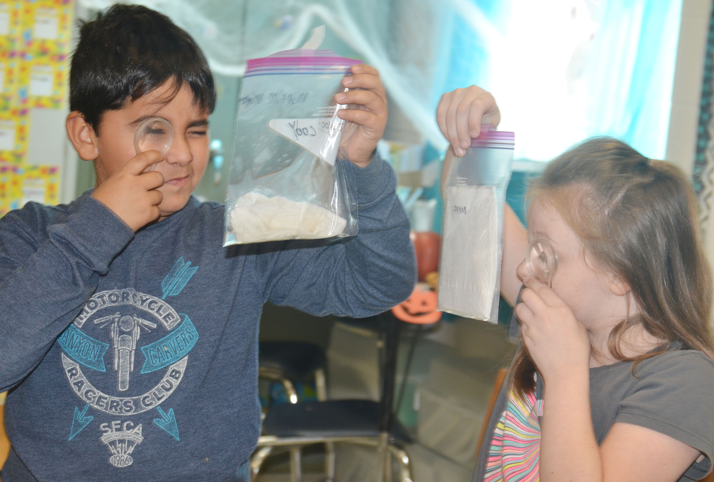 CES third-graders Cody Tamez and Jaylen Clark take a close look at their seeds to see how they've grown over the past few days.