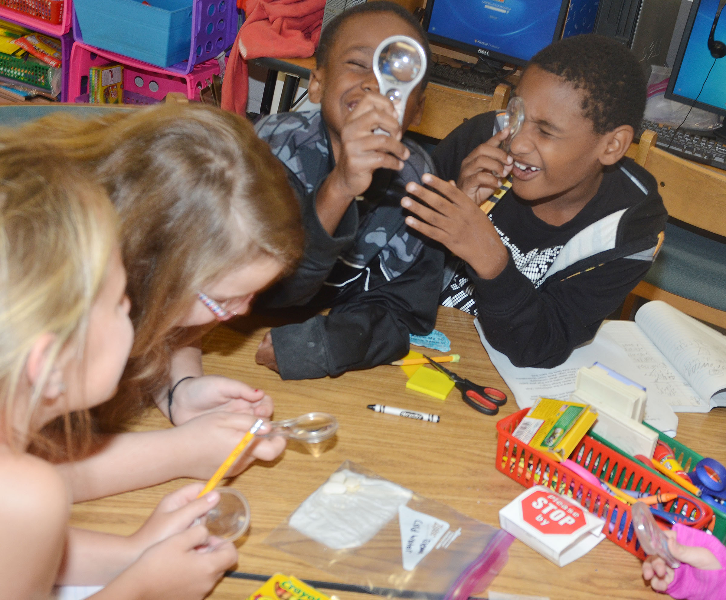 CES third-graders John Gholston, at left, and Shaiden Calhoun work with their teammates to take a close look at their seeds to see how much they've grown.