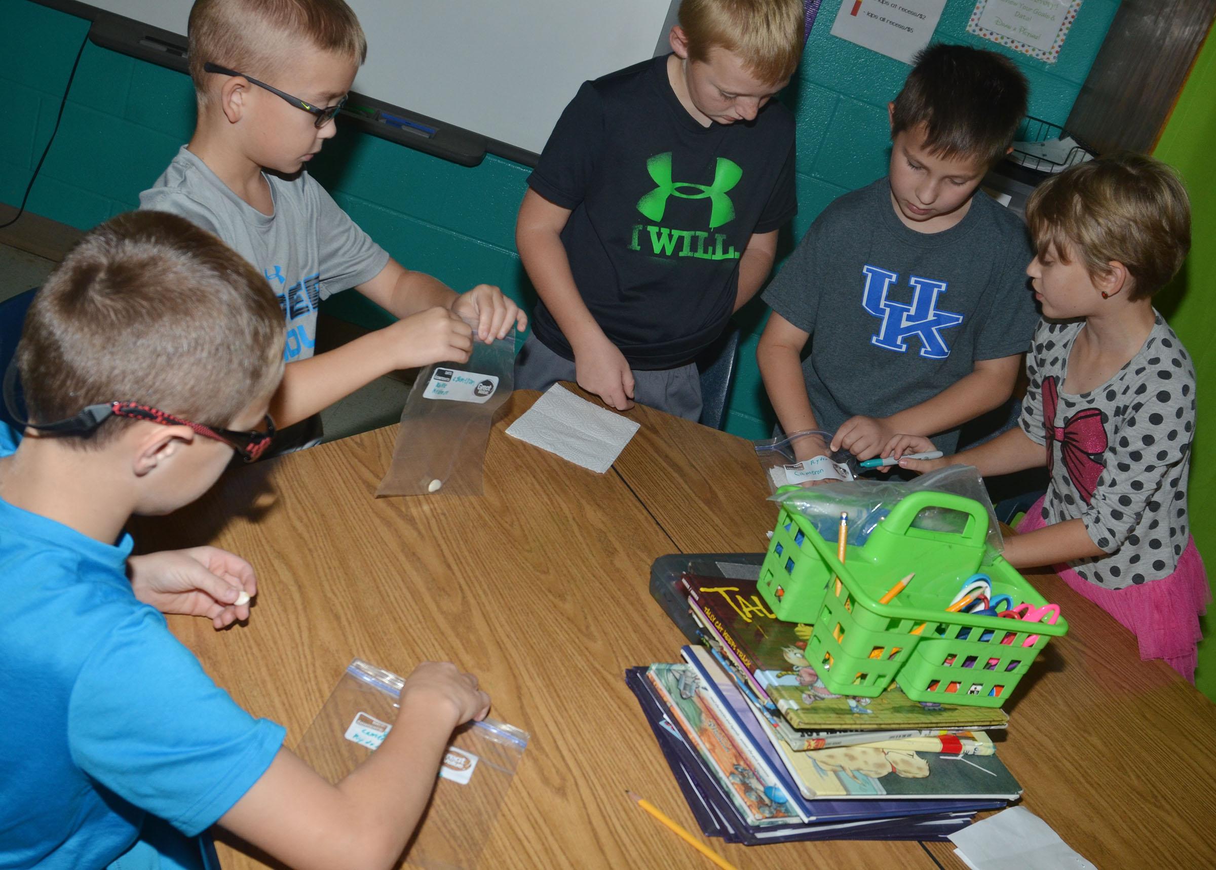 CES third-graders place their seeds in bags so they can determine which elements help them grow the most. From left are Keaton Hord, Cameron Estes, Ryder Murphy, Grayson Dooley and Katie Nunn.