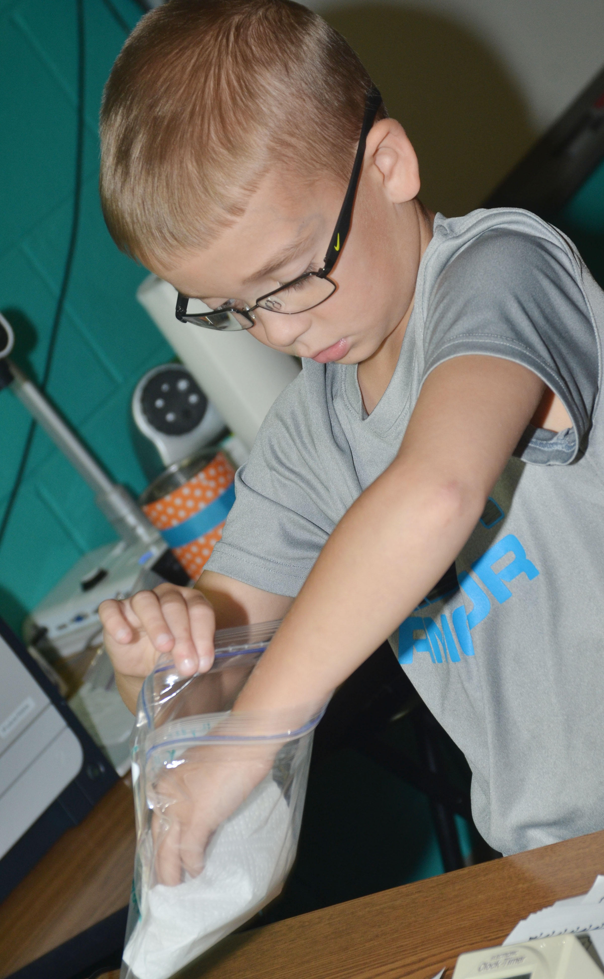 CES third-grader Cameron Estes adds his group's seed to a bag so it can grow.