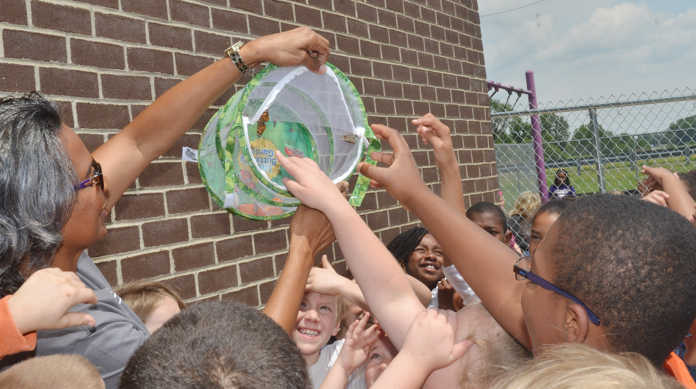 CES third-grade teacher Doretha Sanders holds a container as the butterflies inside prepare to fly away.
