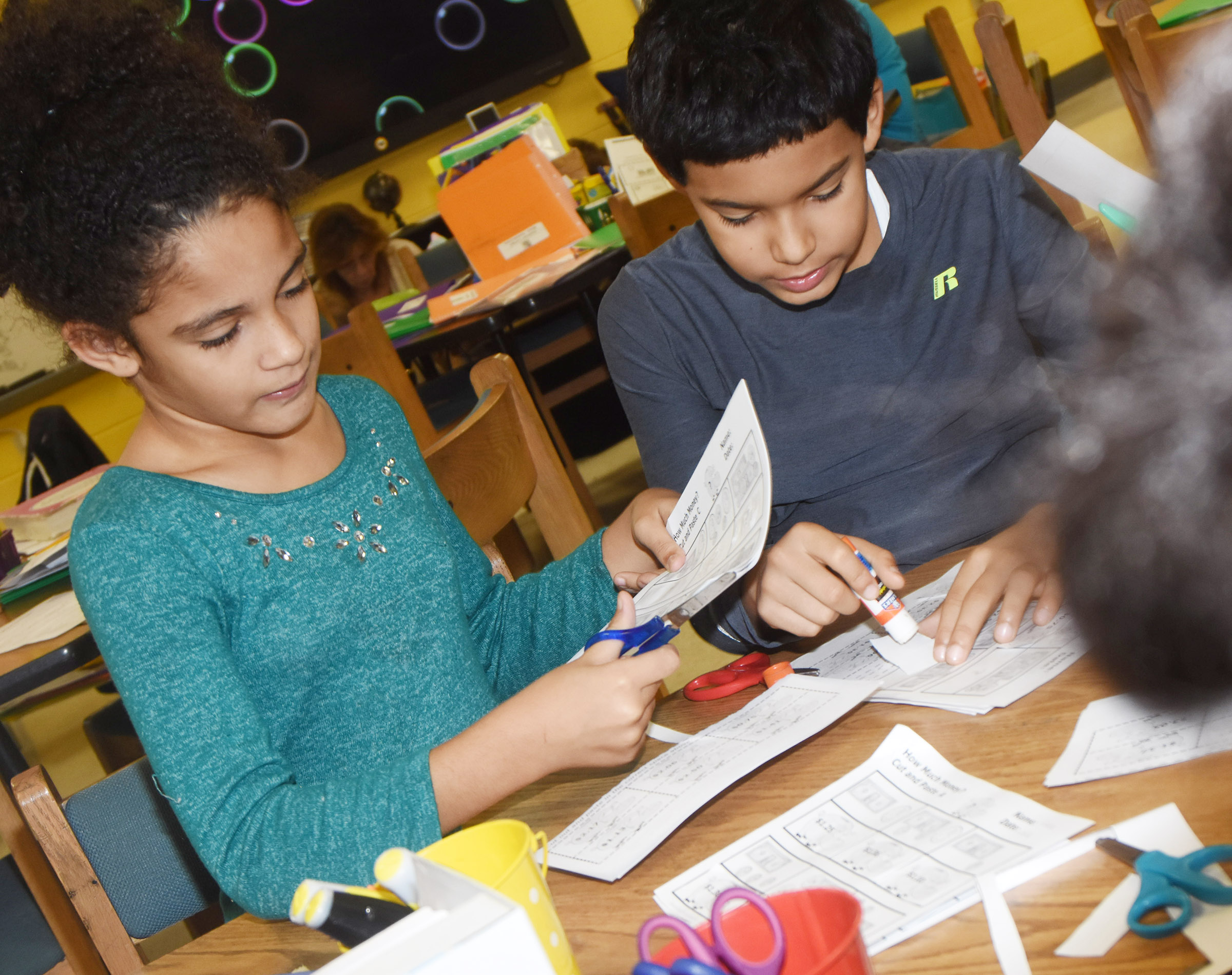 CES third-graders Tierra White, at left, and Rizzo McKenzie glues pictures of money as they practice counting bills and coins.