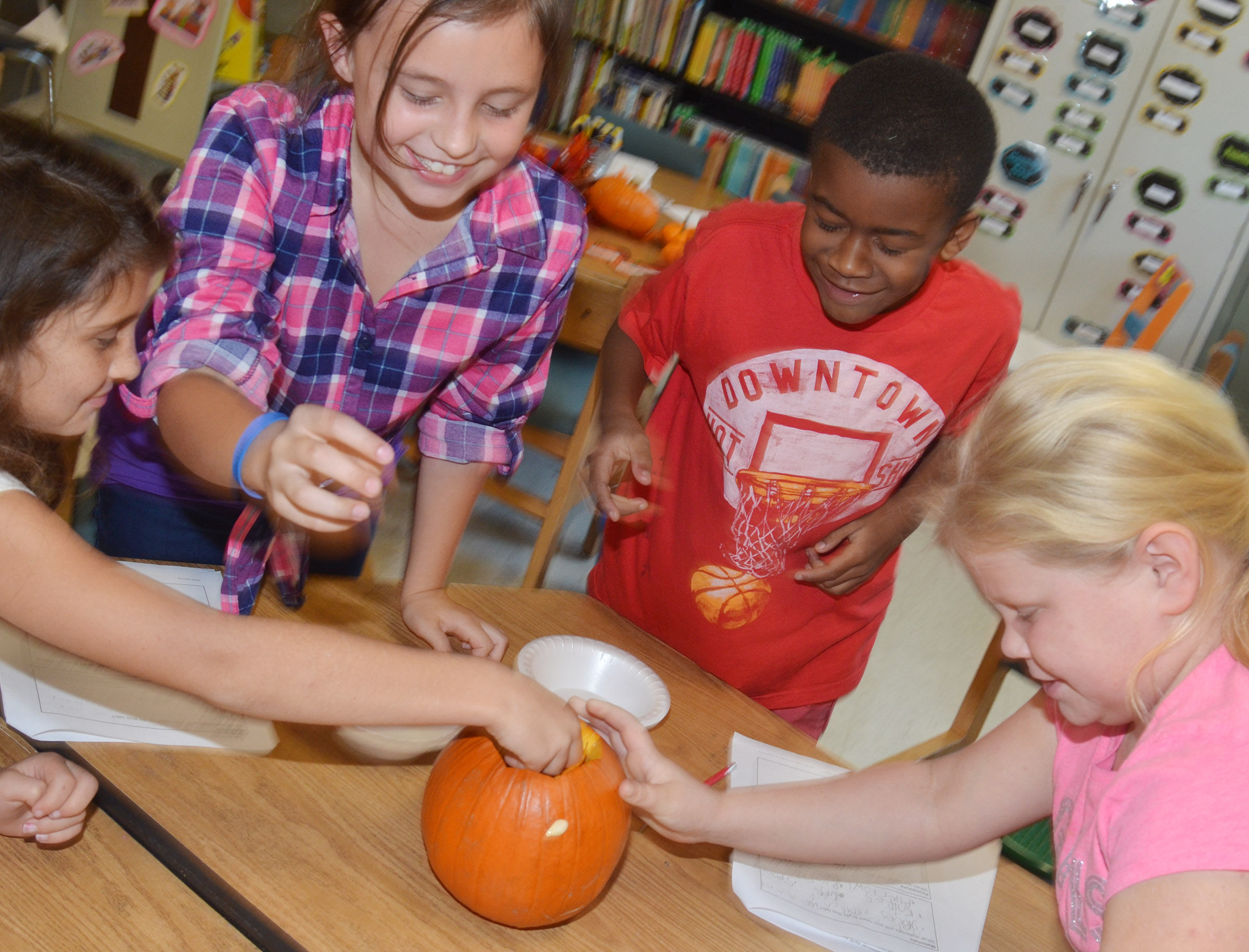 From left, CES third-graders Ava Taylor, Annabelle Brockman, Kae'vin Spaulding and Lily Coots get the seeds out of their pumpkin.