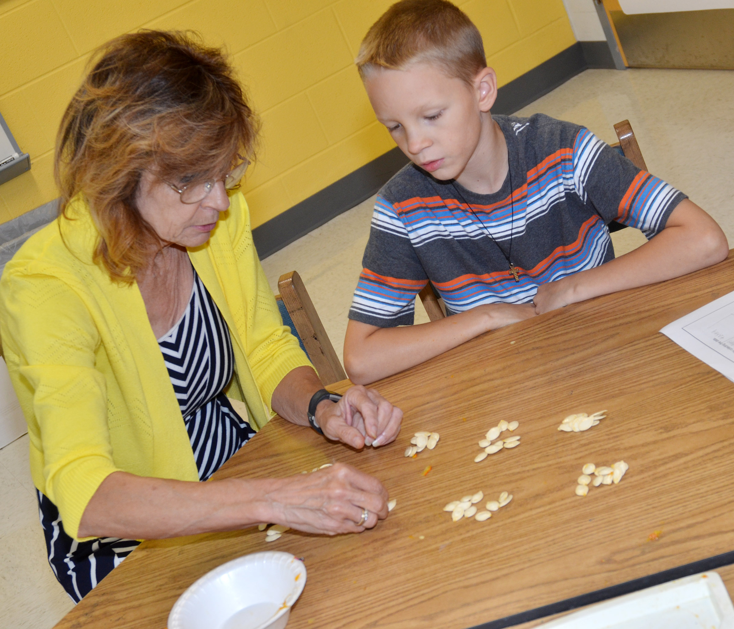 CES third-grade teacher Marcia Sharp helps Braxton Agee count pumpkin seeds.