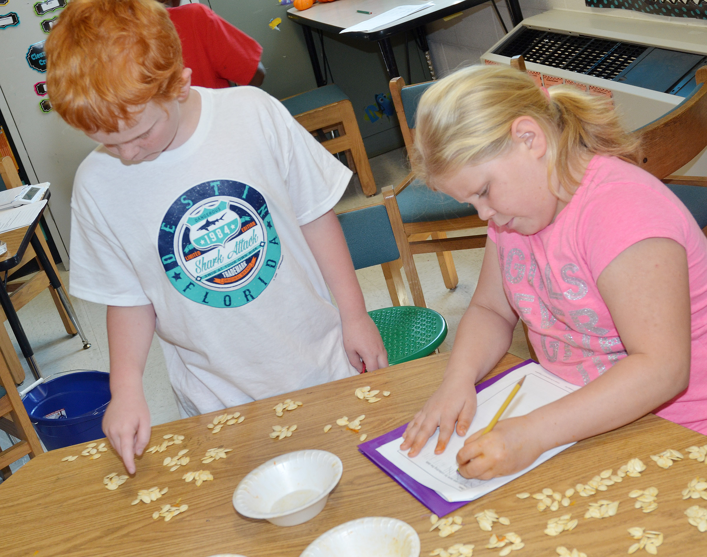 CES third-graders Gavin Martin, at left, and Lily Coots count pumpkin seeds and record their data.