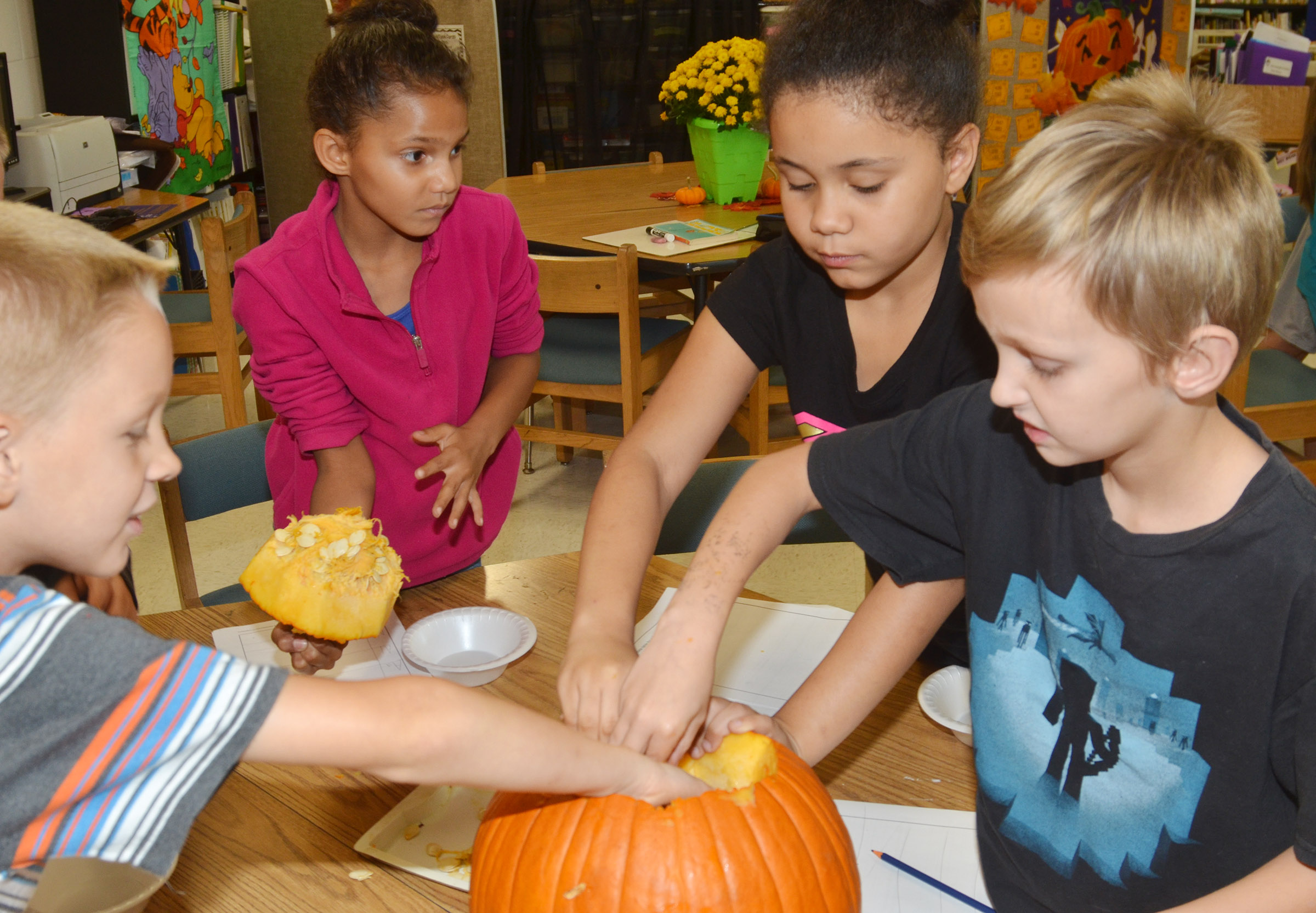 From left, CES third-graders Braxton Agee, Malia Thompson, Alex Wilson and Aaron Ritchie get the seeds out of their pumpkin.