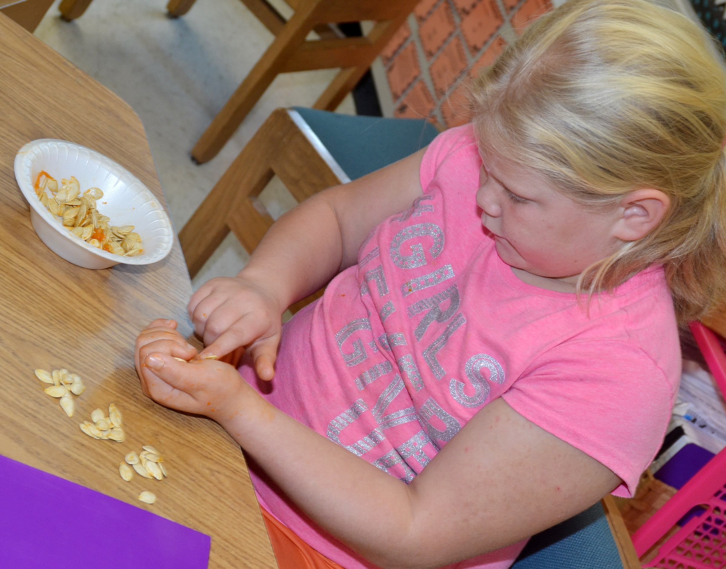 CES third-grader Lily Coots counts pumpkin seeds.