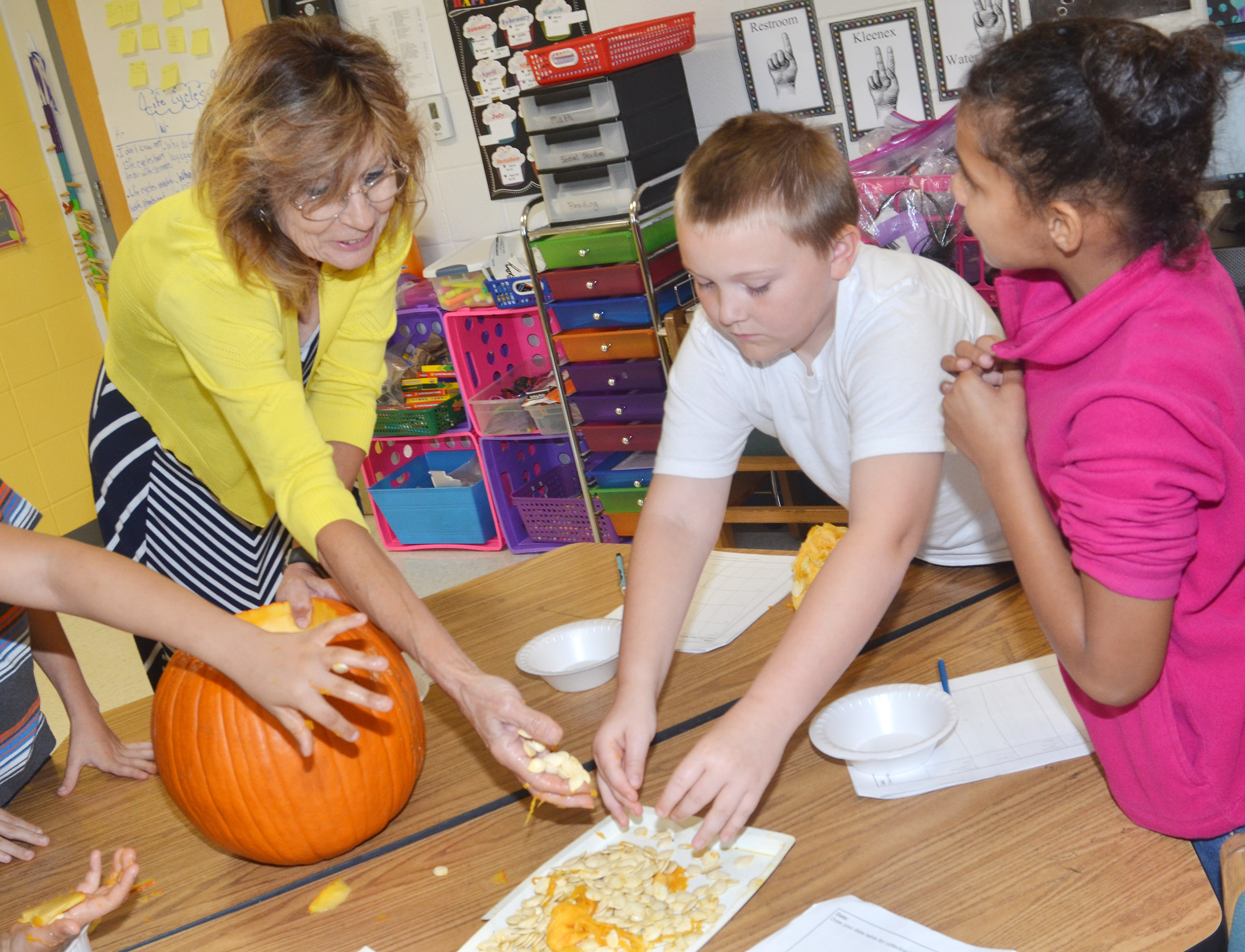 CES third-grade teacher Marcia Sharp helps Griffin Skaggs, at left, and Malia Thompson get the seeds out of their pumpkin.