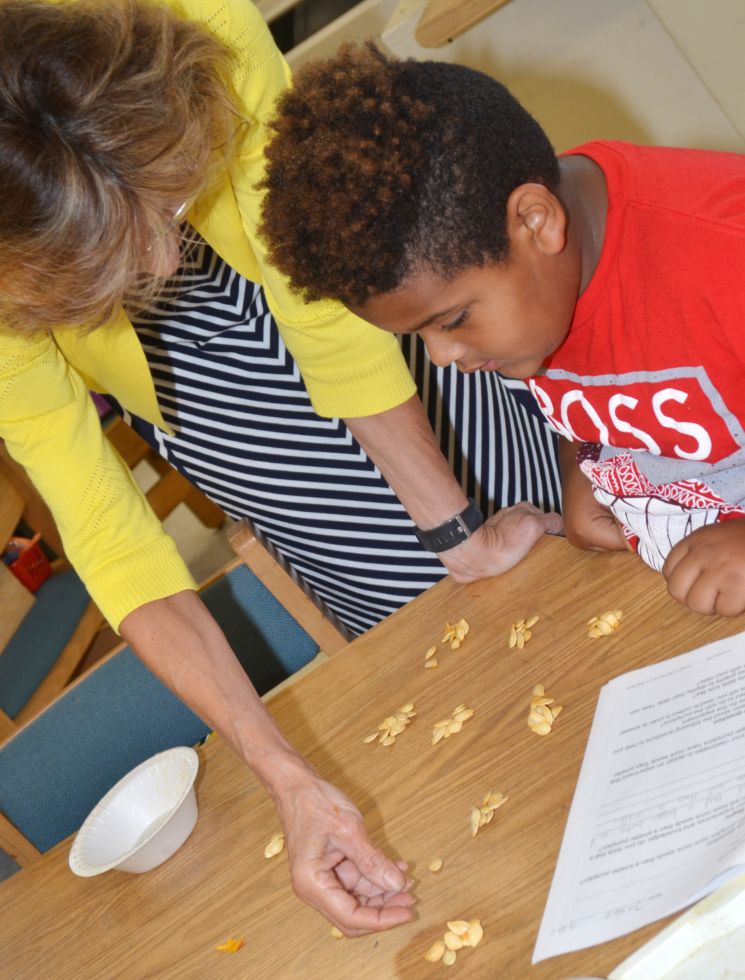 CES third-grade teacher Marcia Sharp helps Jayden Moore count pumpkin seeds.