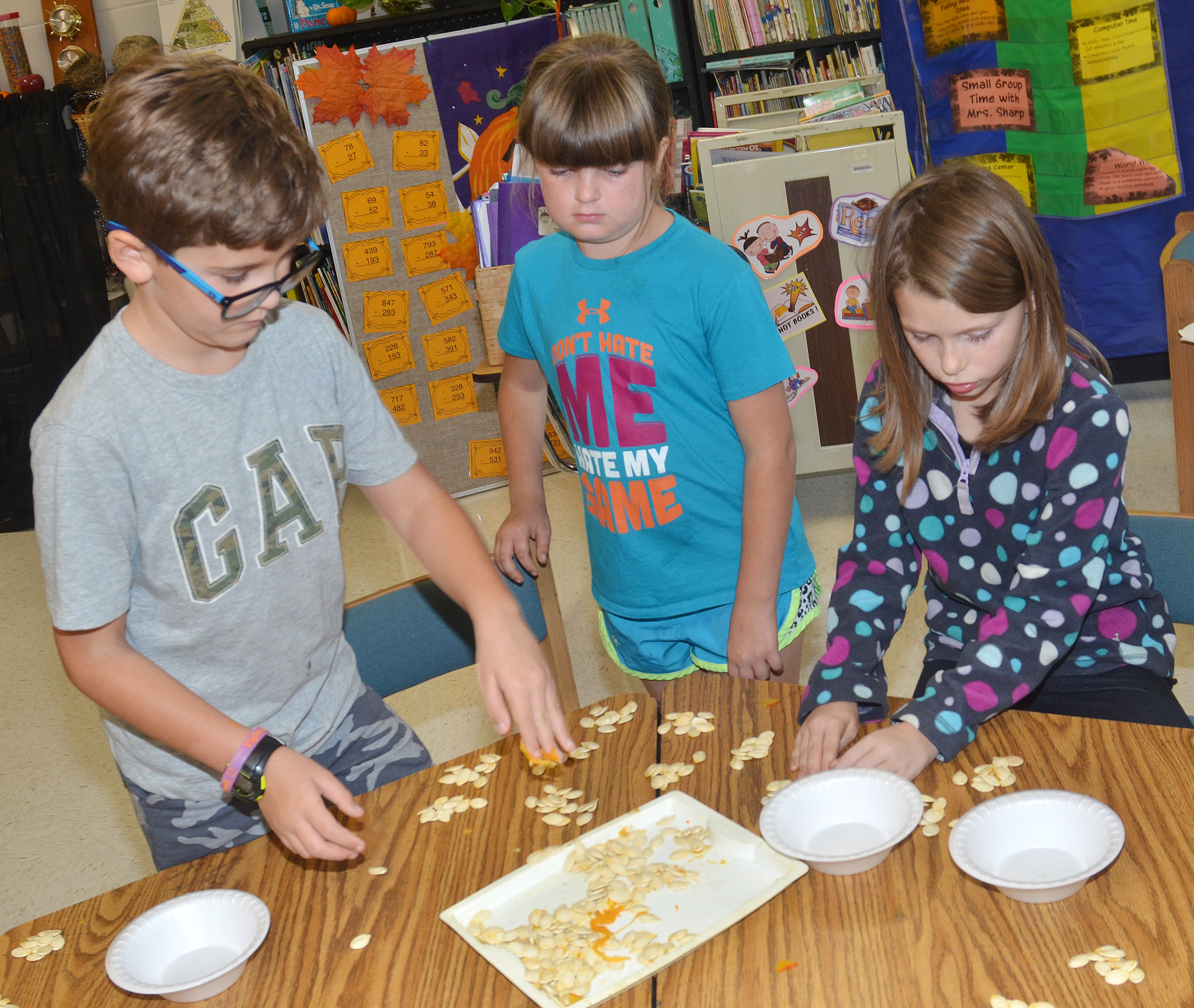 From left, CES third-graders Tye Rhodes, Kaleigh Wilhoite and Sammantha Wooley count pumpkin seeds.