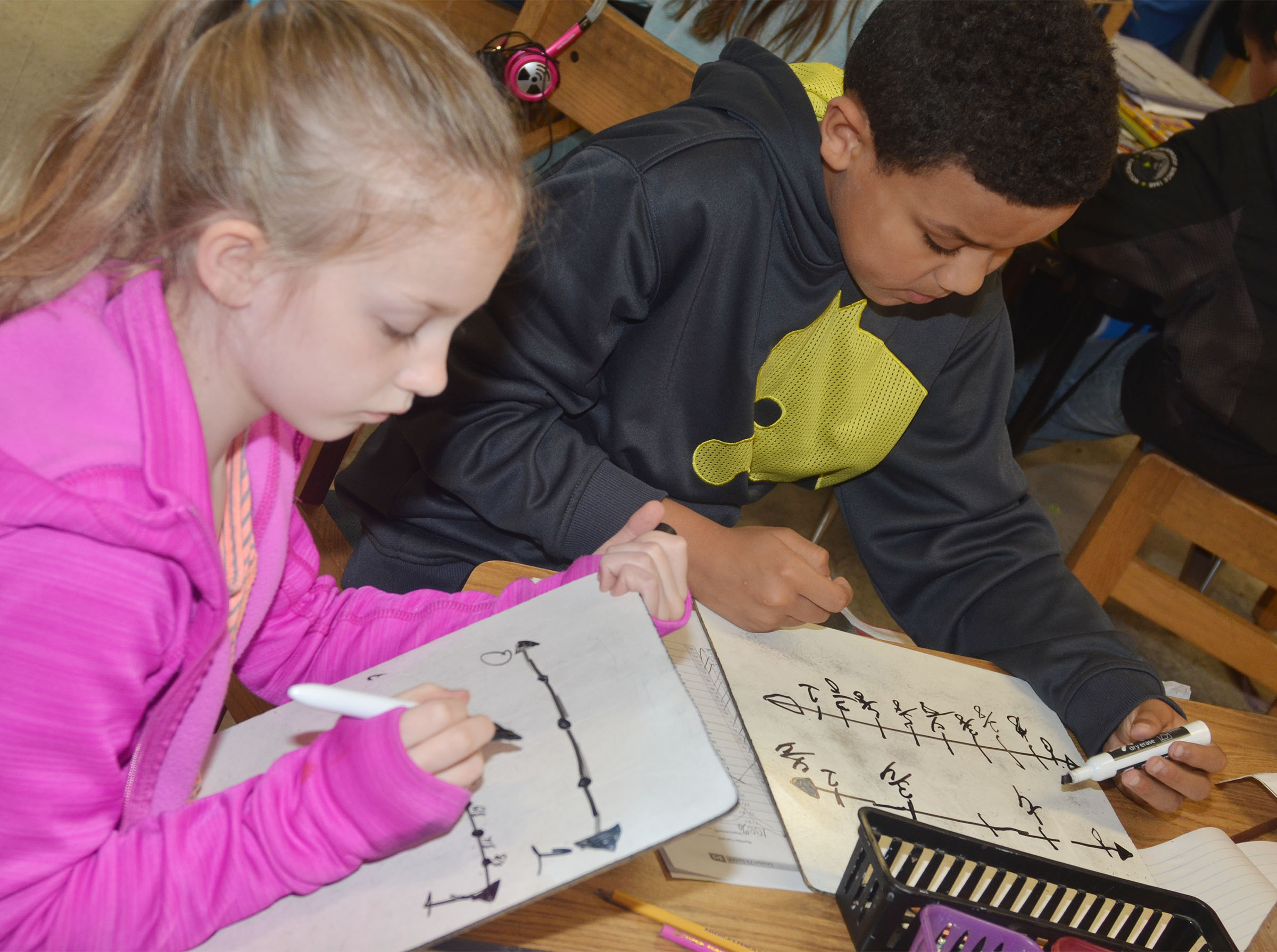 CES third-graders Kendall Bright, at left, and Christian Hart practice adding fractions.