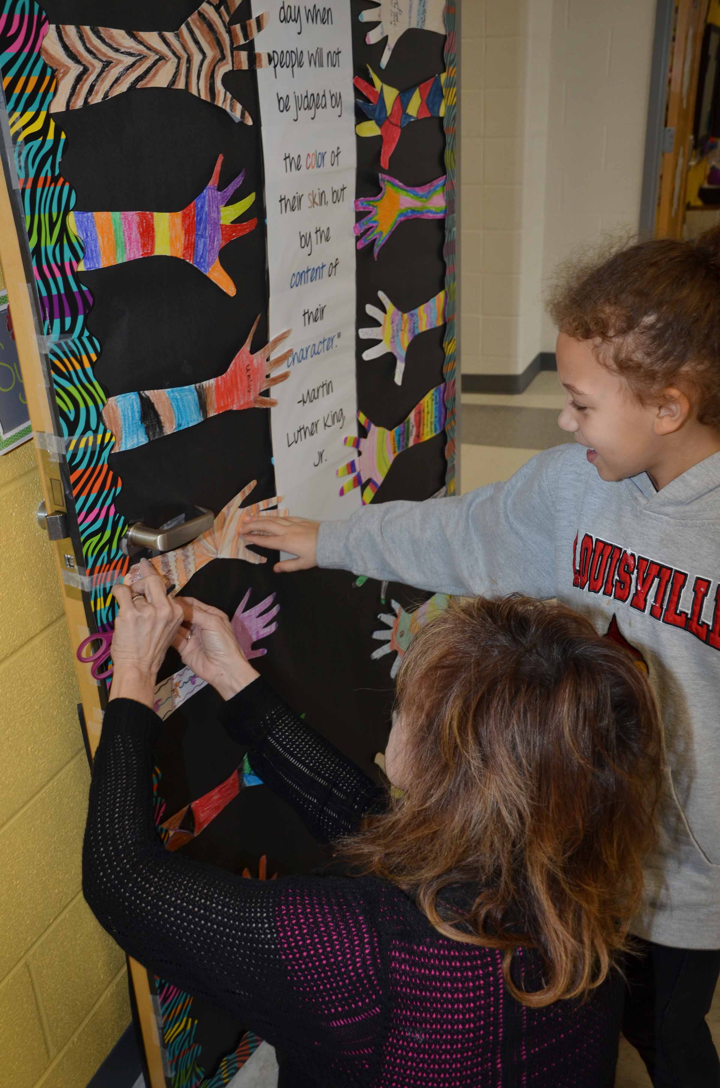 CES third-grade teacher Marcia Sharp hangs the hand that third-grader Alicia Spaulding decorated.