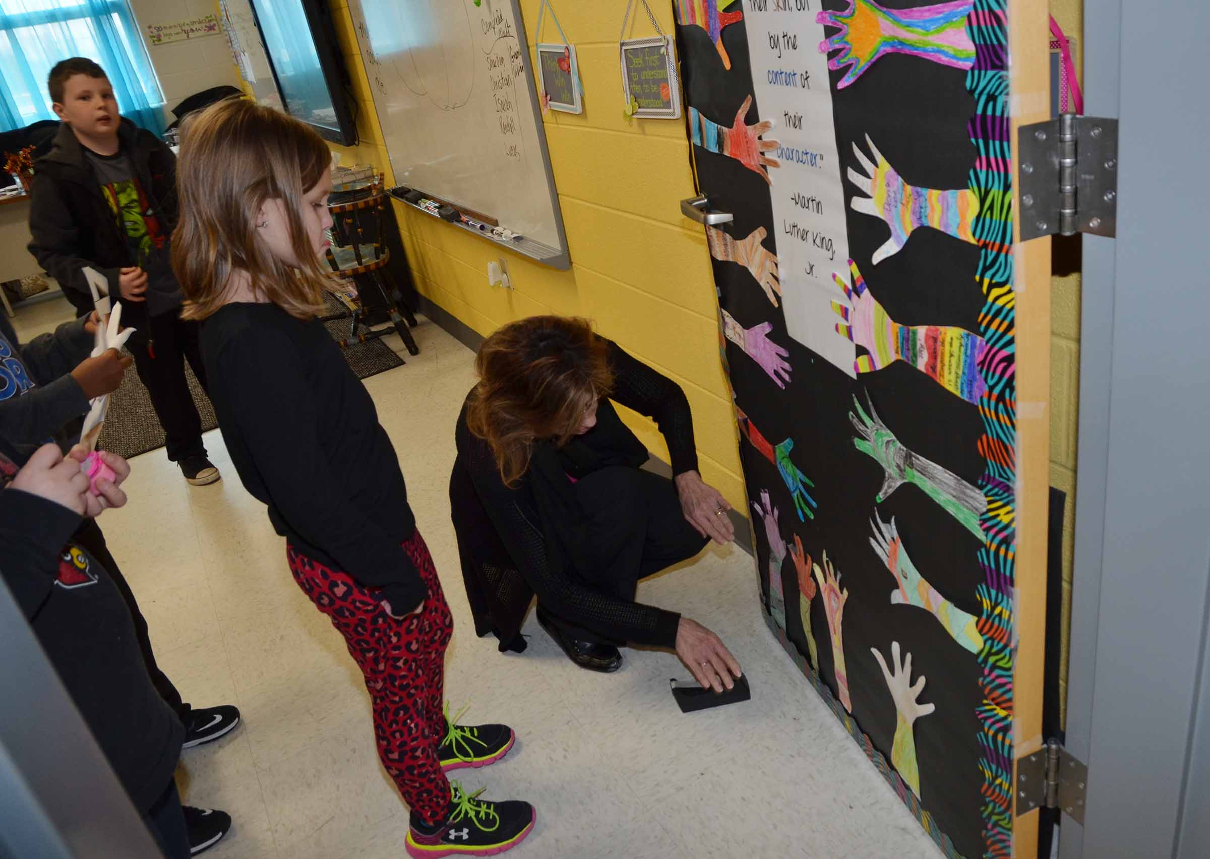 Students watch as CES third-grade teacher Marcia Sharp tapes hands to her classroom door.