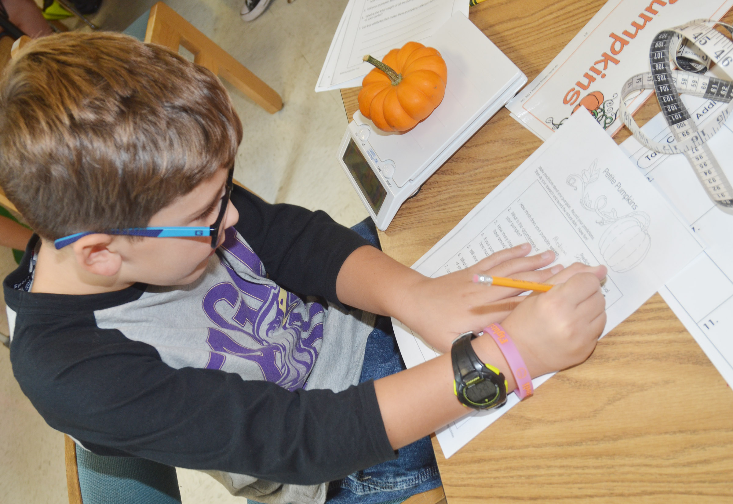 CES third-grader Tye Rhodes records the weight of his pumpkin.
