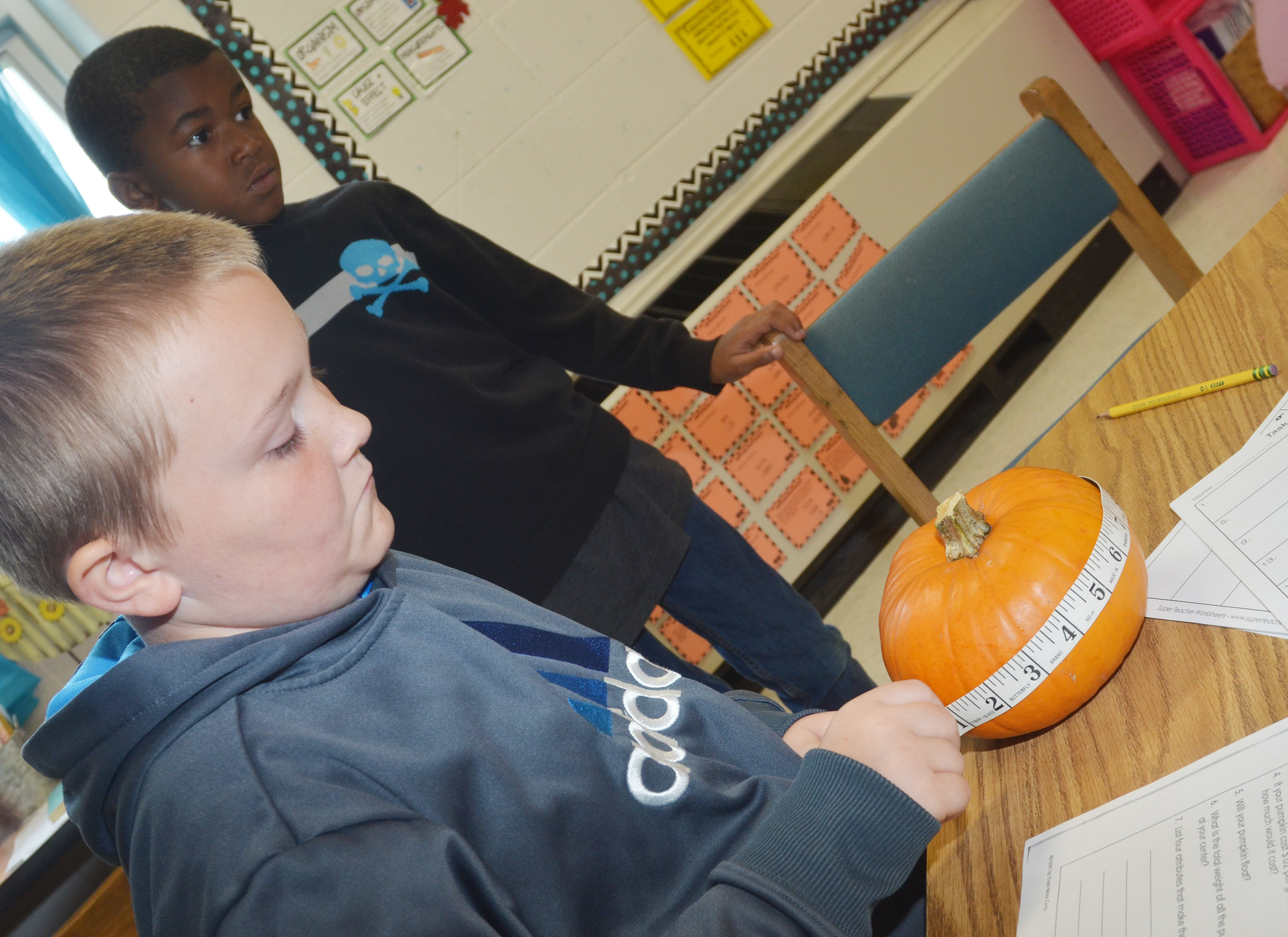 CES third-grader Griffin Skaggs measures his pumpkin as classmate Kae'vin Spaulding waits his turn.