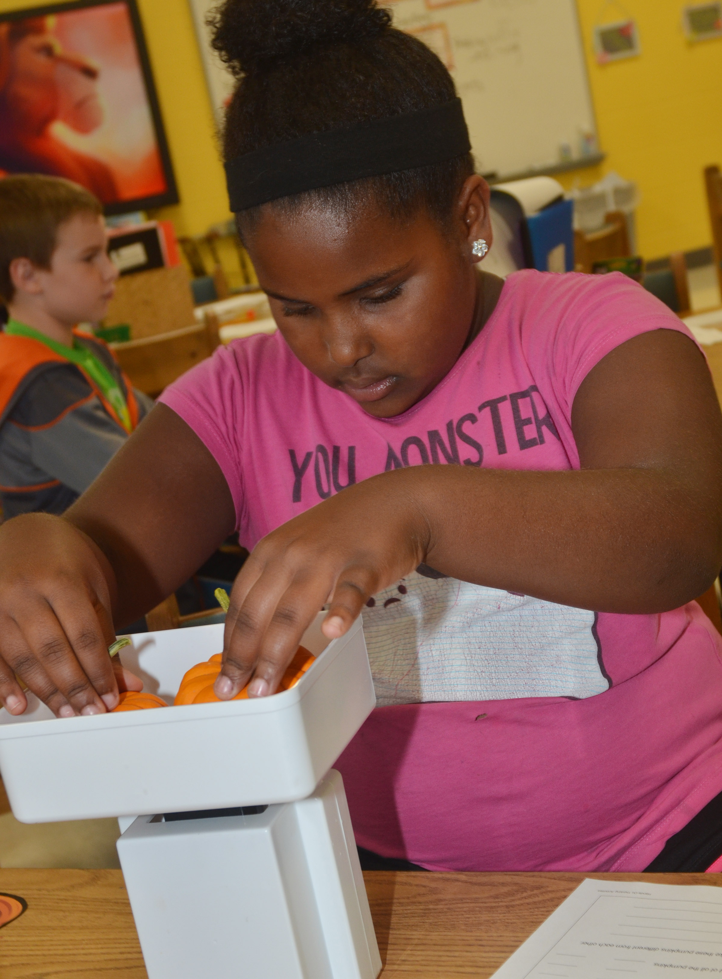 CES third-grader Ajada Smith weighs her pumpkins.