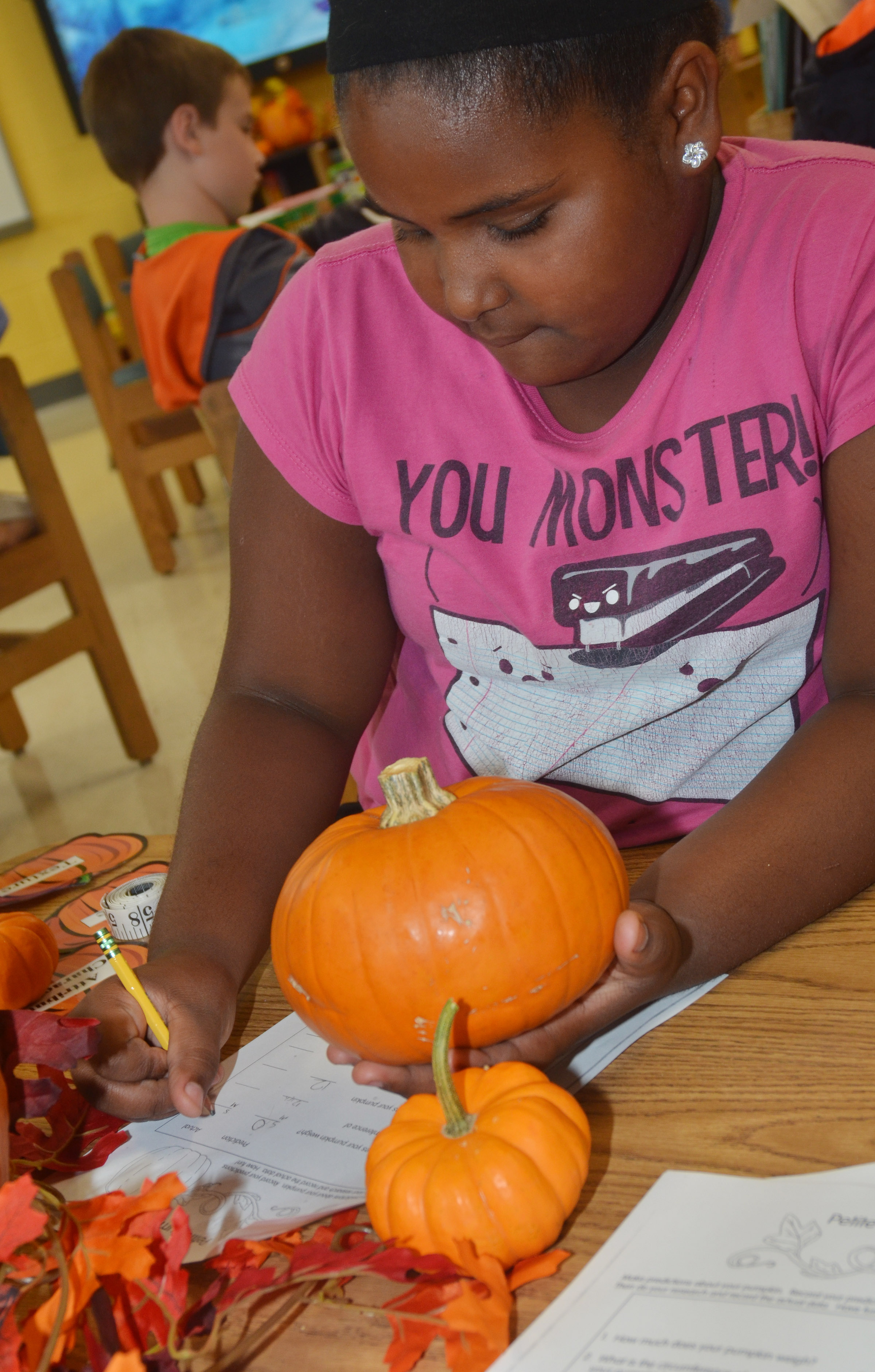 CES third-grader Ajada Smith records data about her pumpkins.
