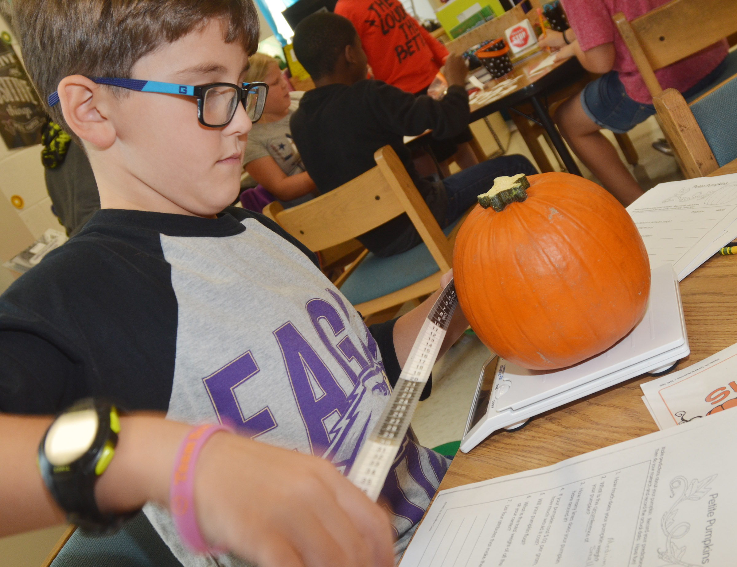 CES third-grader Tye Rhodes measures his pumpkin.