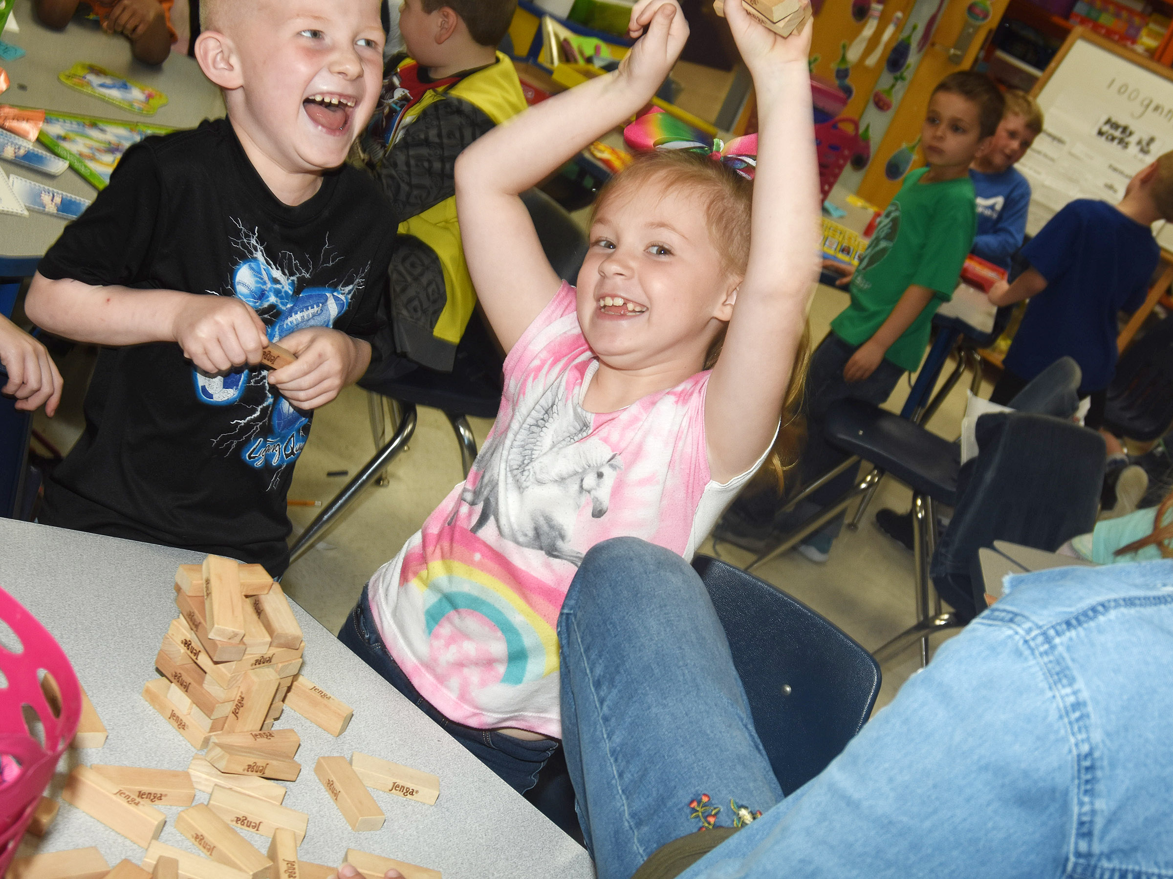 CES first-graders Jayden Maupin, at left, and Ava Caffee laugh as their Jenga pieces fall during a game with teacher Luci Shofner.