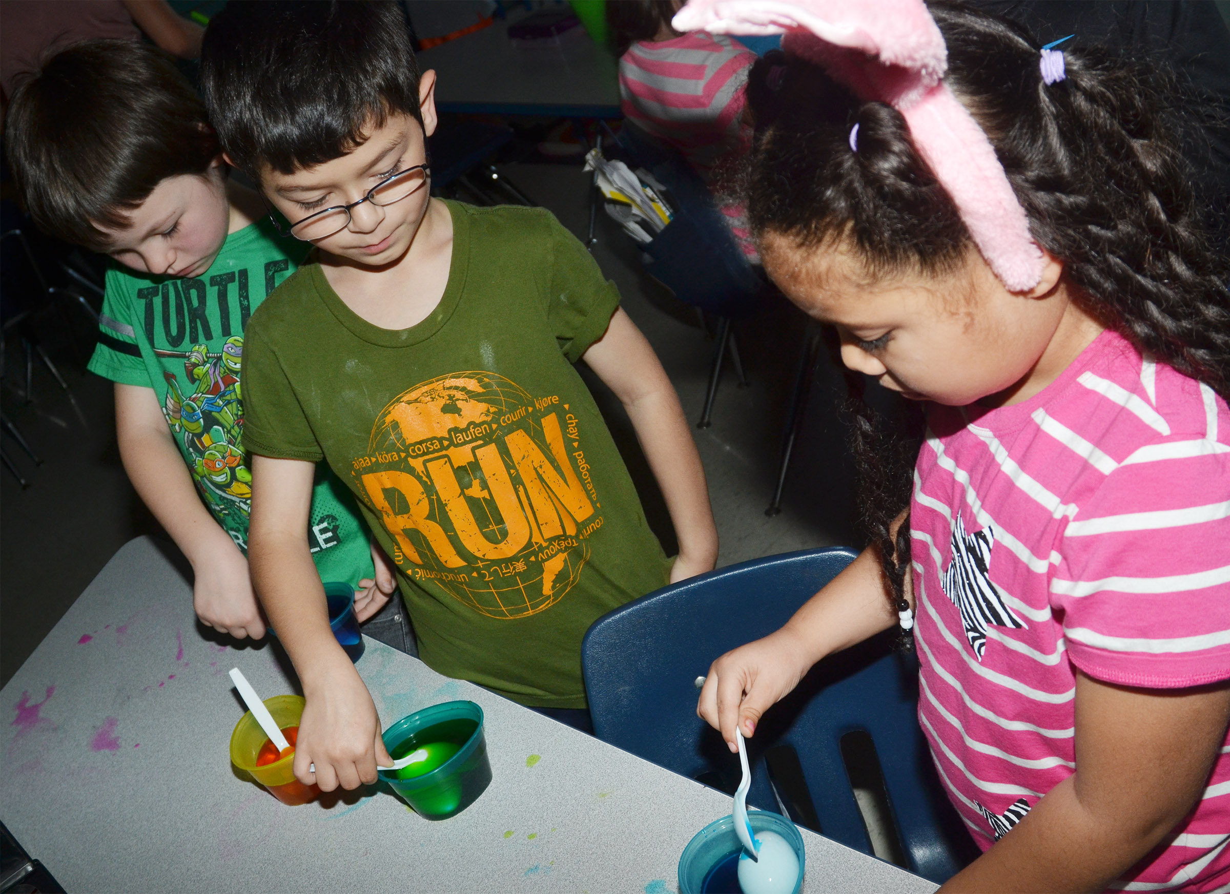 From left, CES first-graders Joseph Boudreaux, Henry Martinez and Briana Wooley dye their Easter eggs.