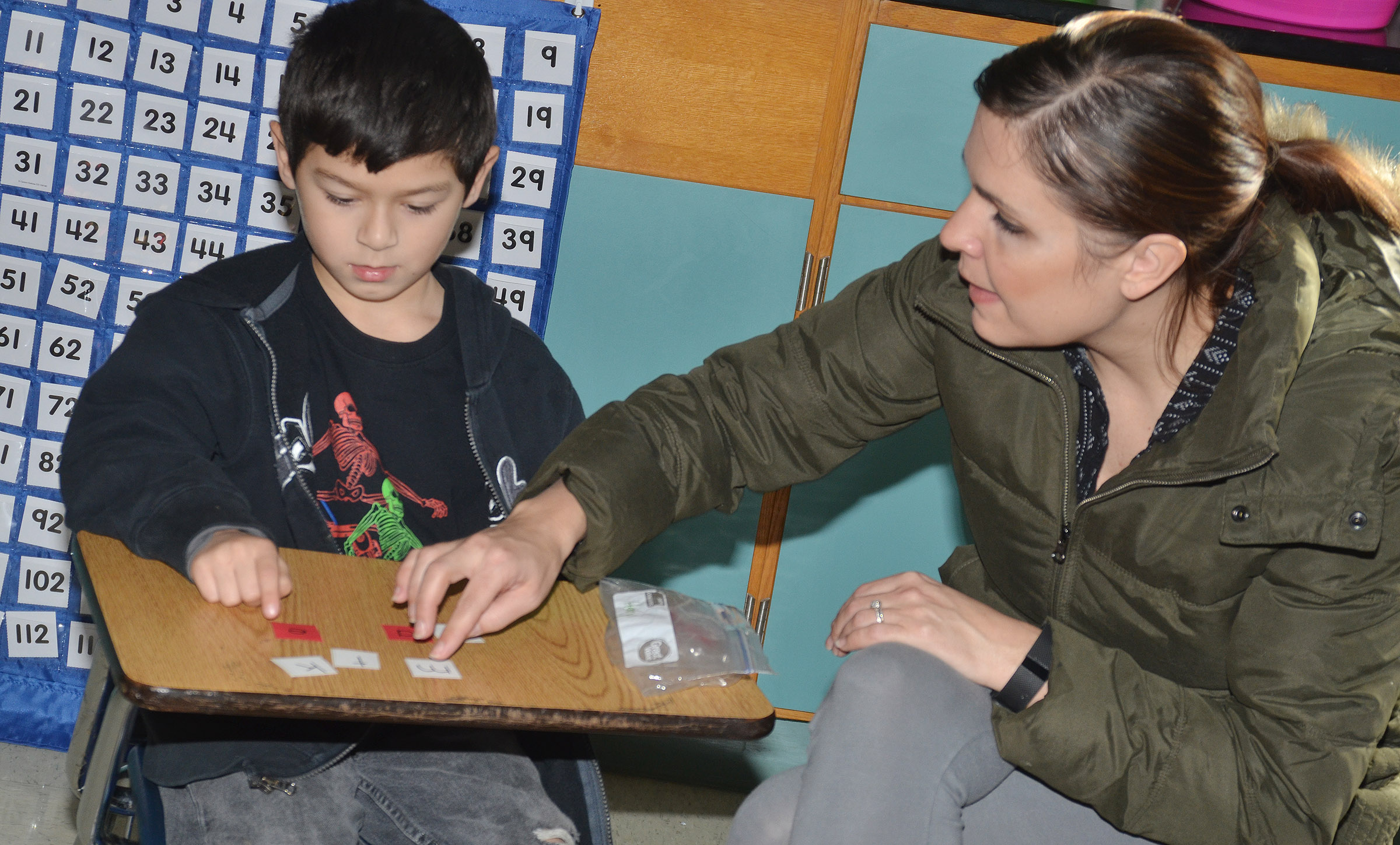 "CES first-grade teacher Luci Shofner helps Henry Martinez spell ""make."""