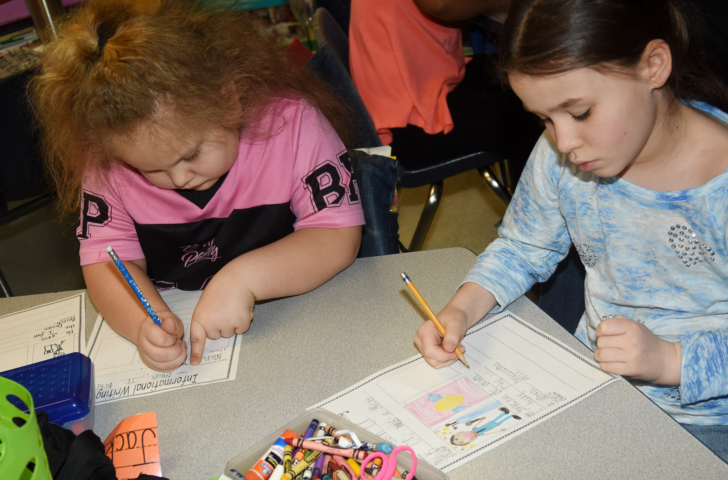CES first-graders ReAnna Jeffries, at left, and Stella Newcomb write about Dr. Martin Luther King Jr.