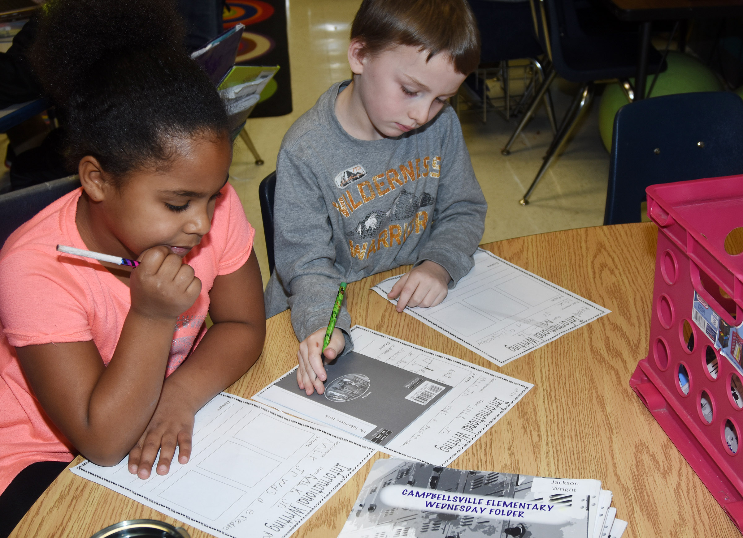 CES first-graders Raelin Goddard, at left, and Ronnie Allen write about Dr. Martin Luther King Jr.