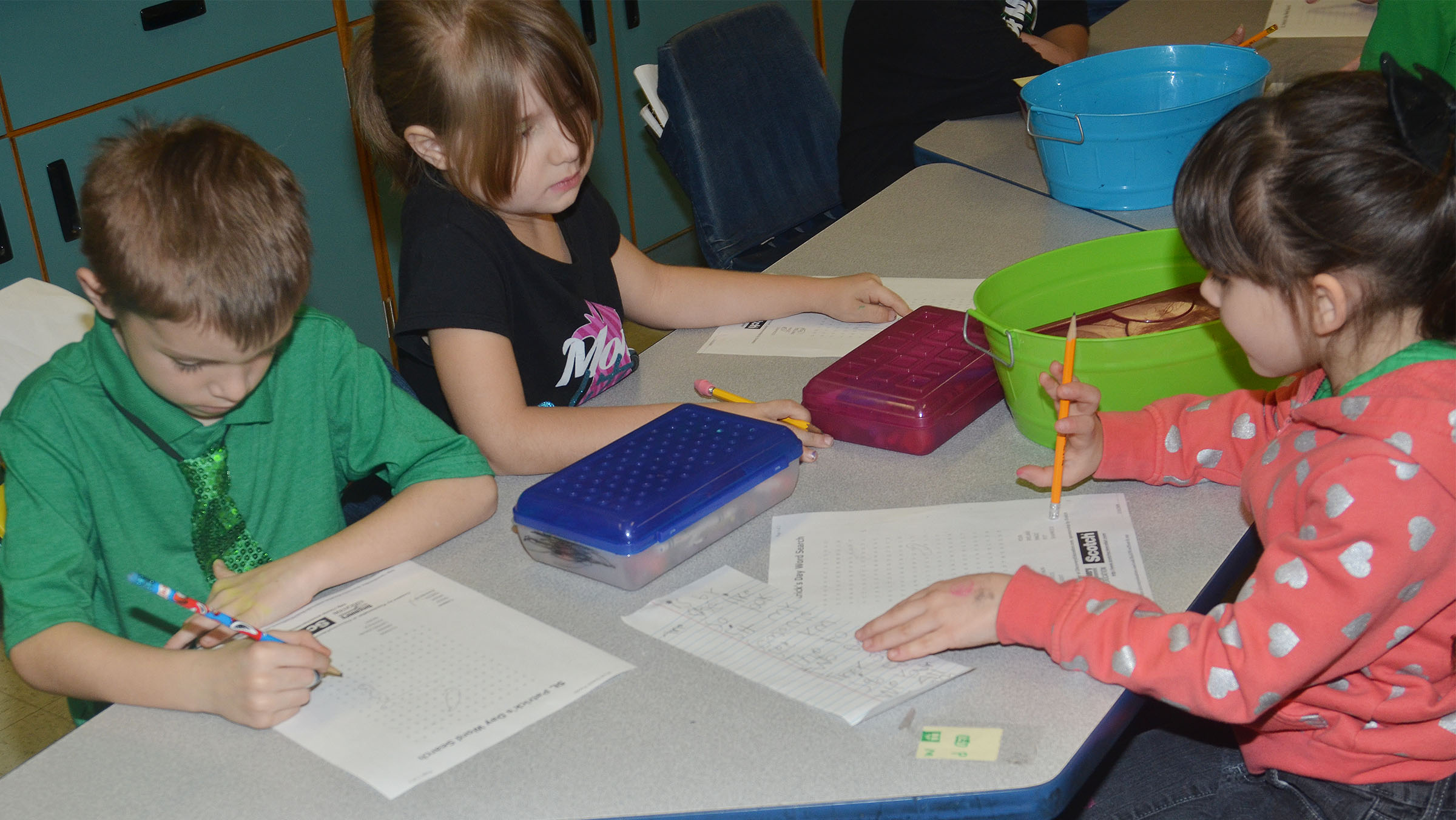 From left, CES first-graders Ben Lord, Kenady Hayes and Phoebe Ritchie work a St. Patrick's Day-themed word search puzzle.