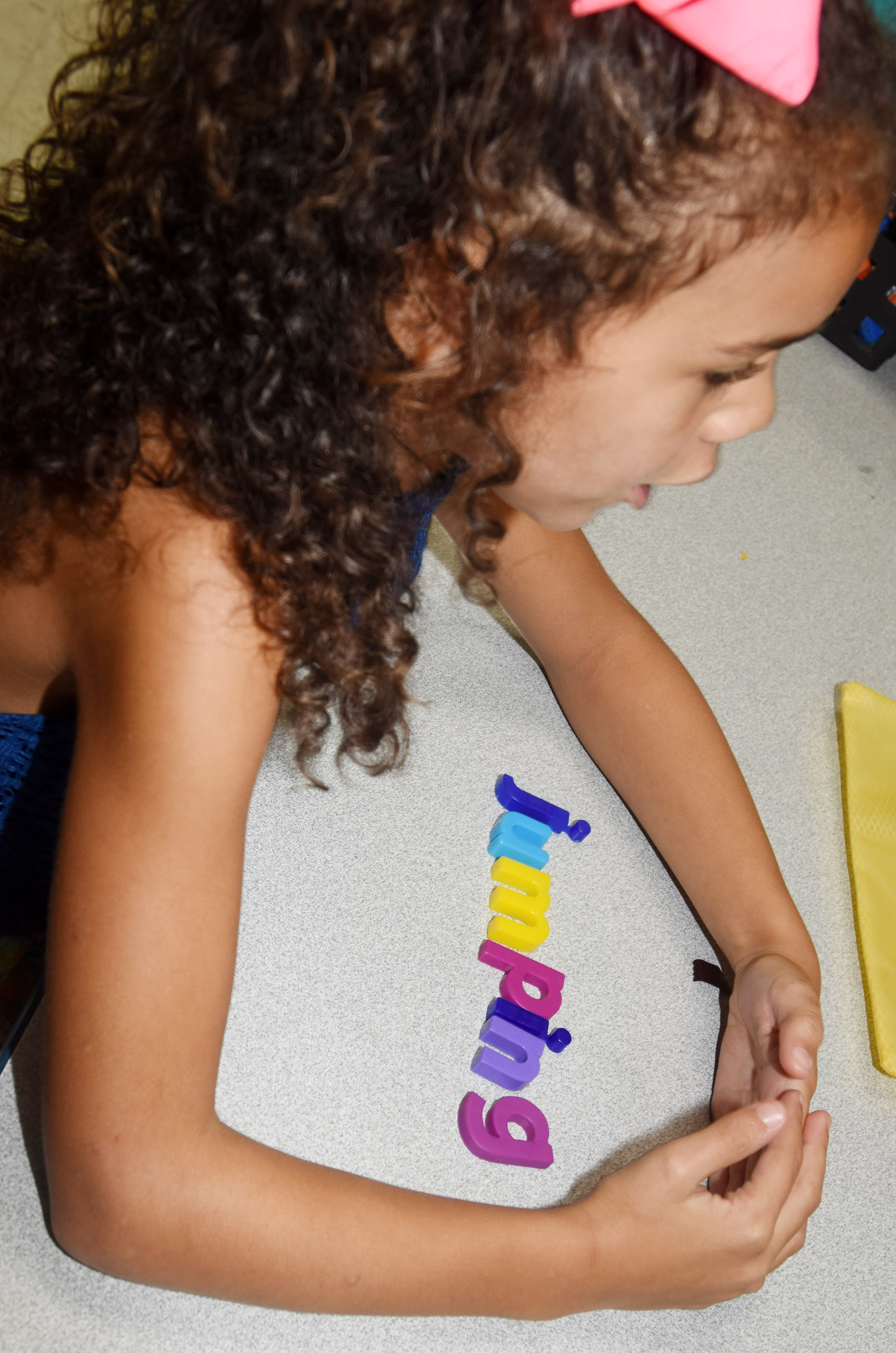 "CES first-grader Adelyn Litsey uses her magnets to spelling the bonus word, ""jumping."""