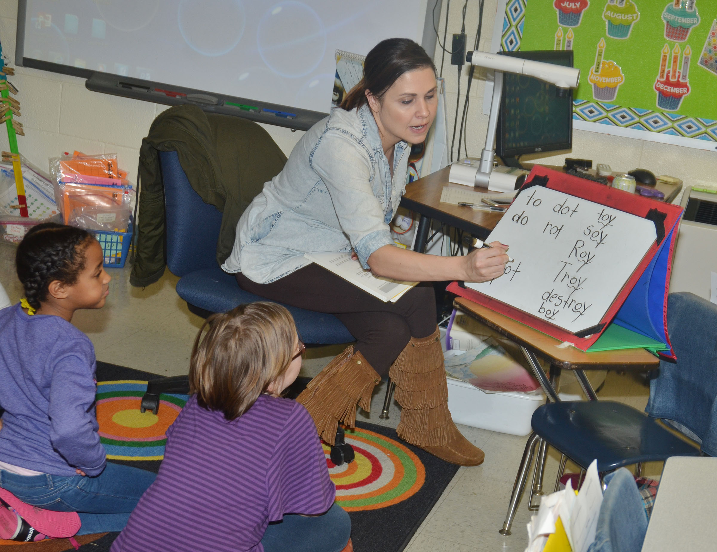 "CES first-grade teacher Luci Shofner talks to her students about words that end in ""oy"" and ""ot."""