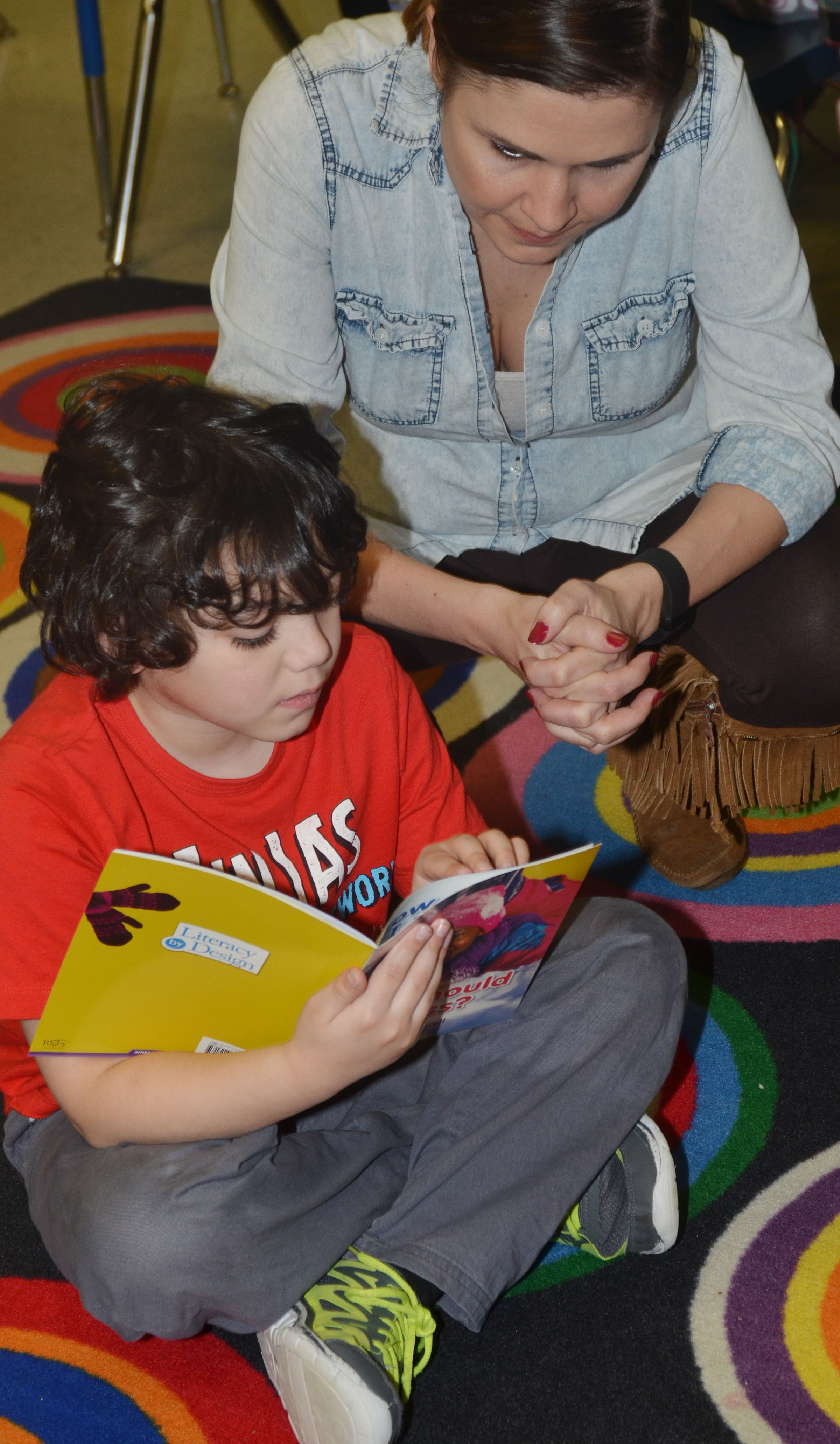 CES first-grader Diego Aquino reads with teacher Luci Shofner.