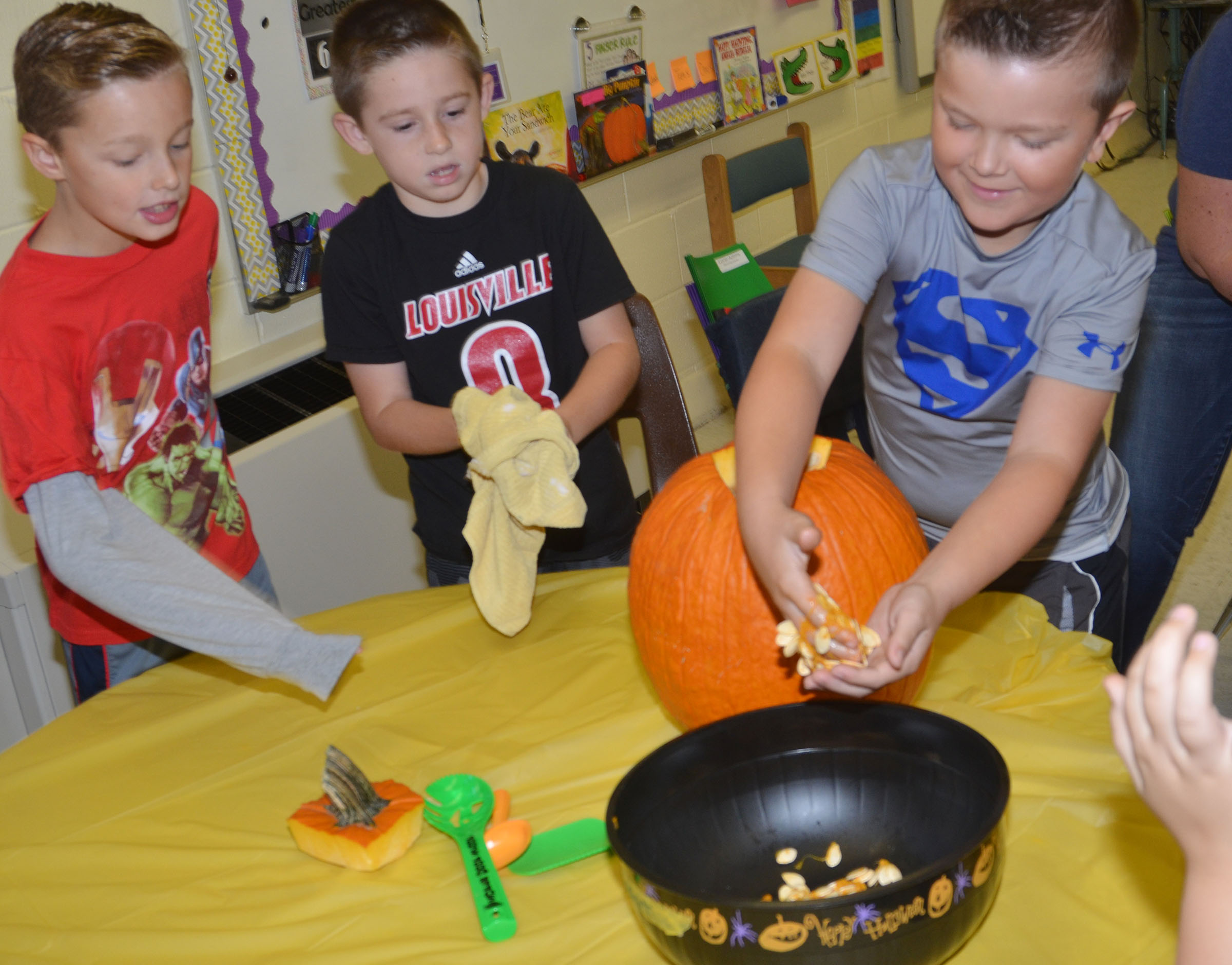 CES second-grader Cayton Lawhorn scoops the seeds out of a pumpkin as his classmates Guy Proctor, at left, and Lanigan Price watch.