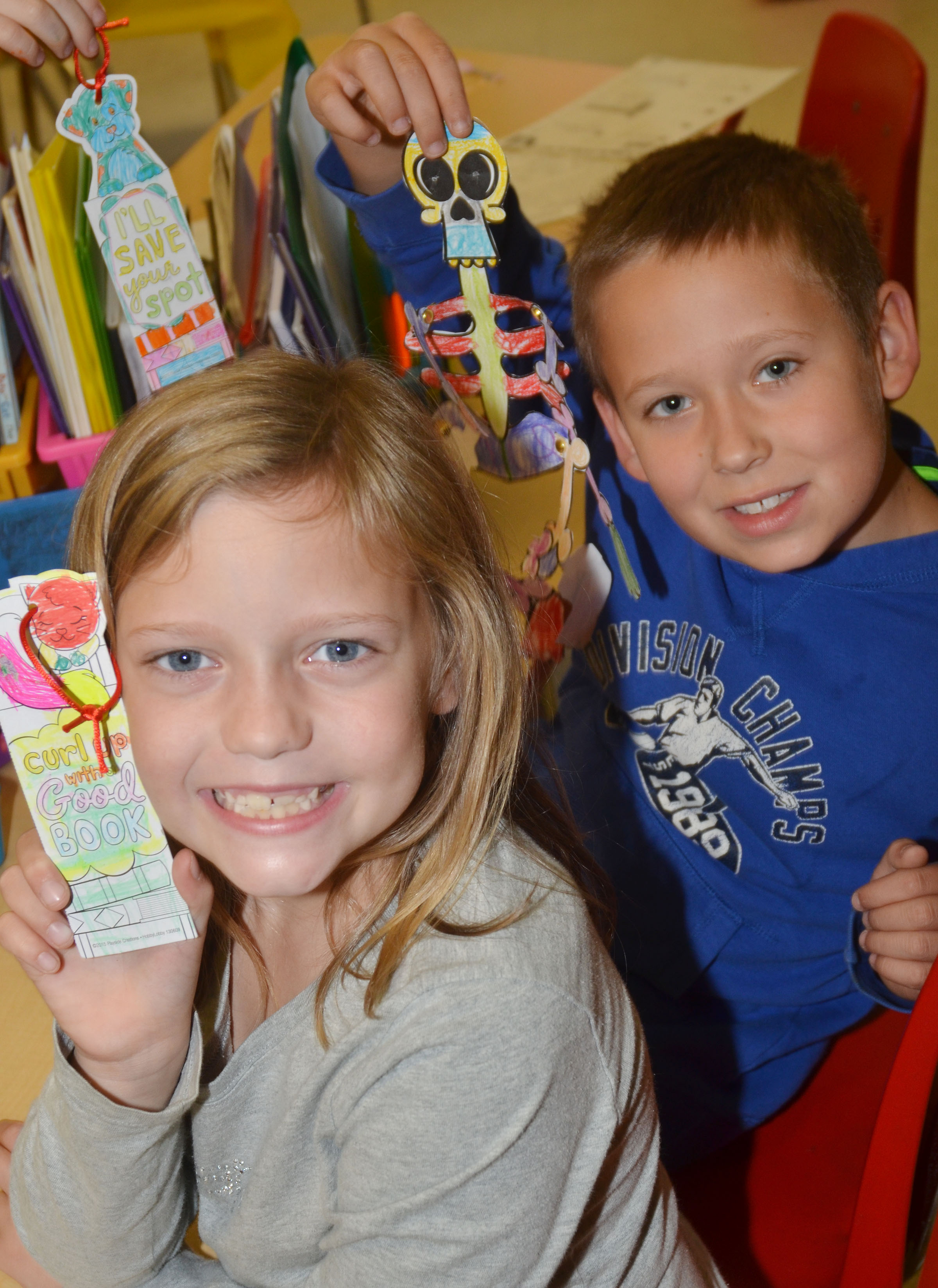 CES second-graders Brooklyn Williamson, at left, and Emerson Dengel hold their finished skeleton and bookmarks.