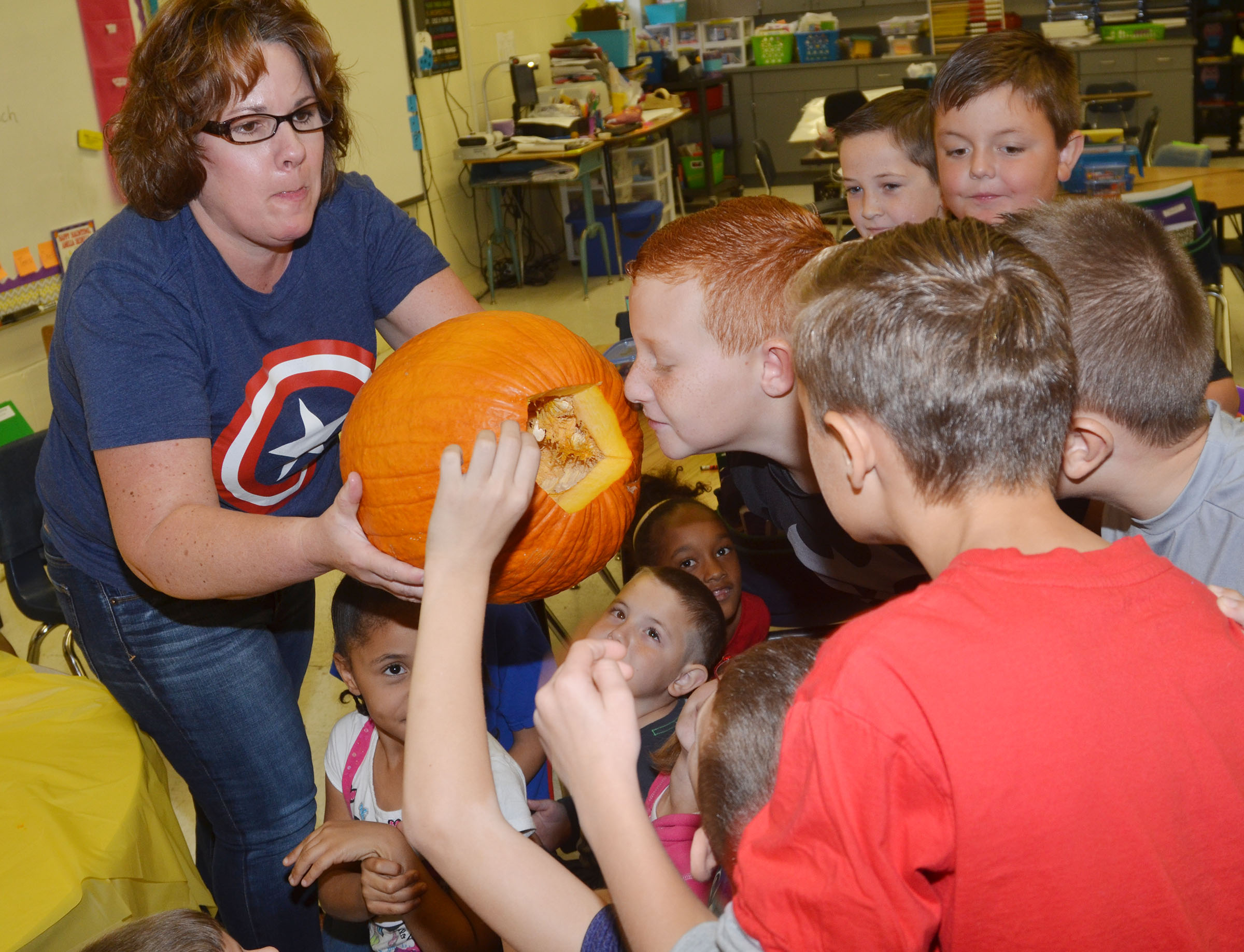 CES second-grade teacher Tracey Rinehart shows her students the inside of a pumpkin.