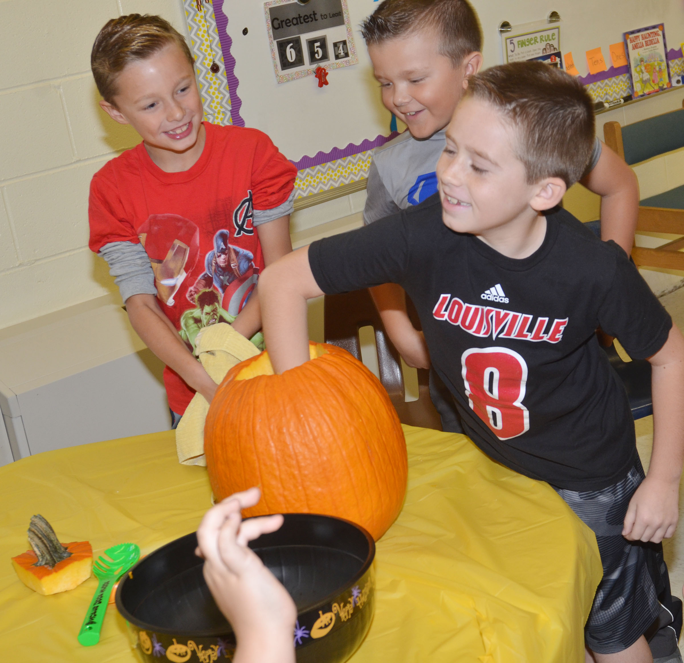 CES second-grader Lanigan Price scoops the seeds out of a pumpkin.