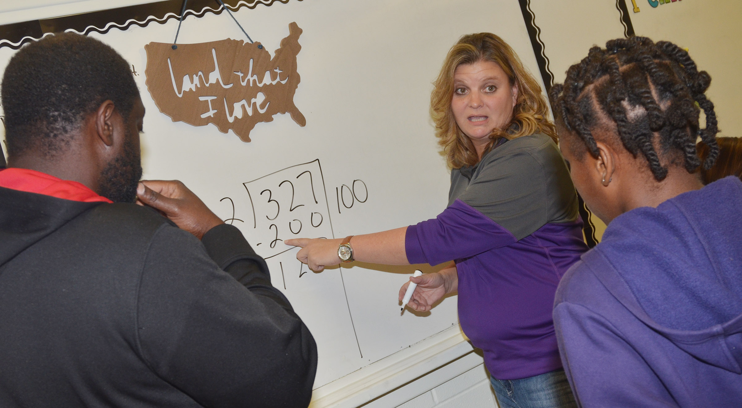 CES fifth-grade teacher Tammy Hash talks to Ta'Zaria Owens and her father Travis about a math concept.
