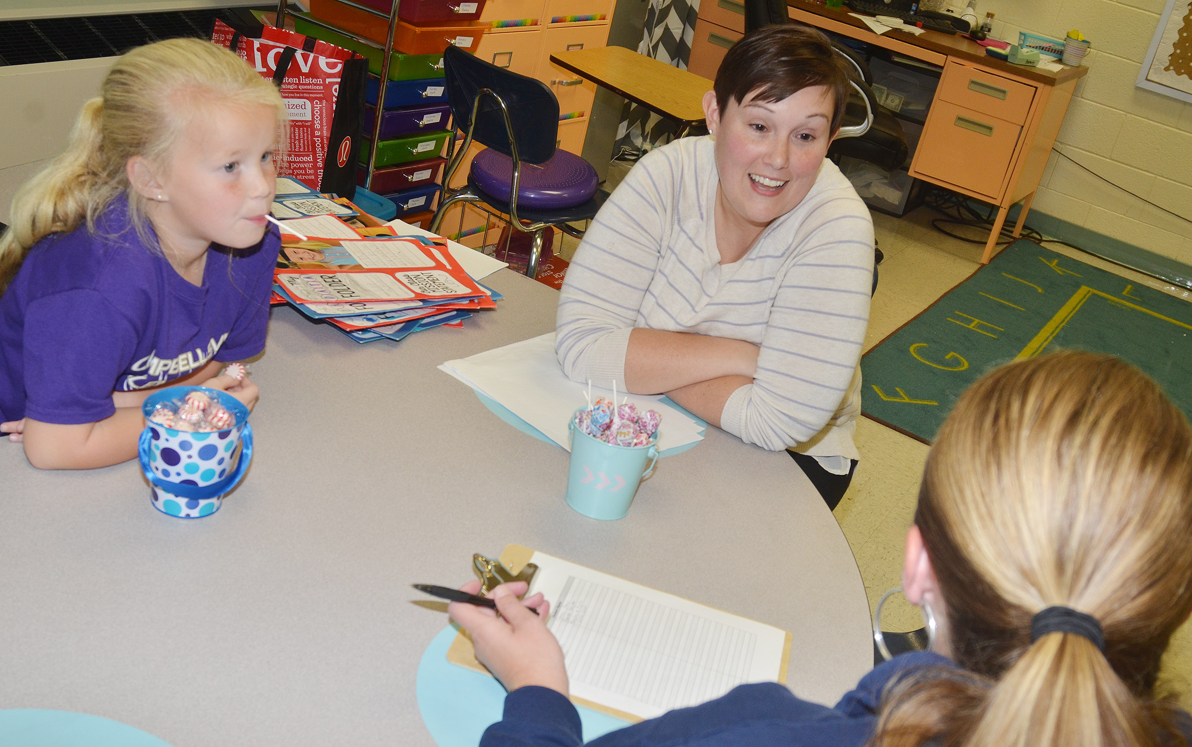 CES first-grade teacher Amanda Barnett talks with Lillie Judd and her mother Jessica Watson.