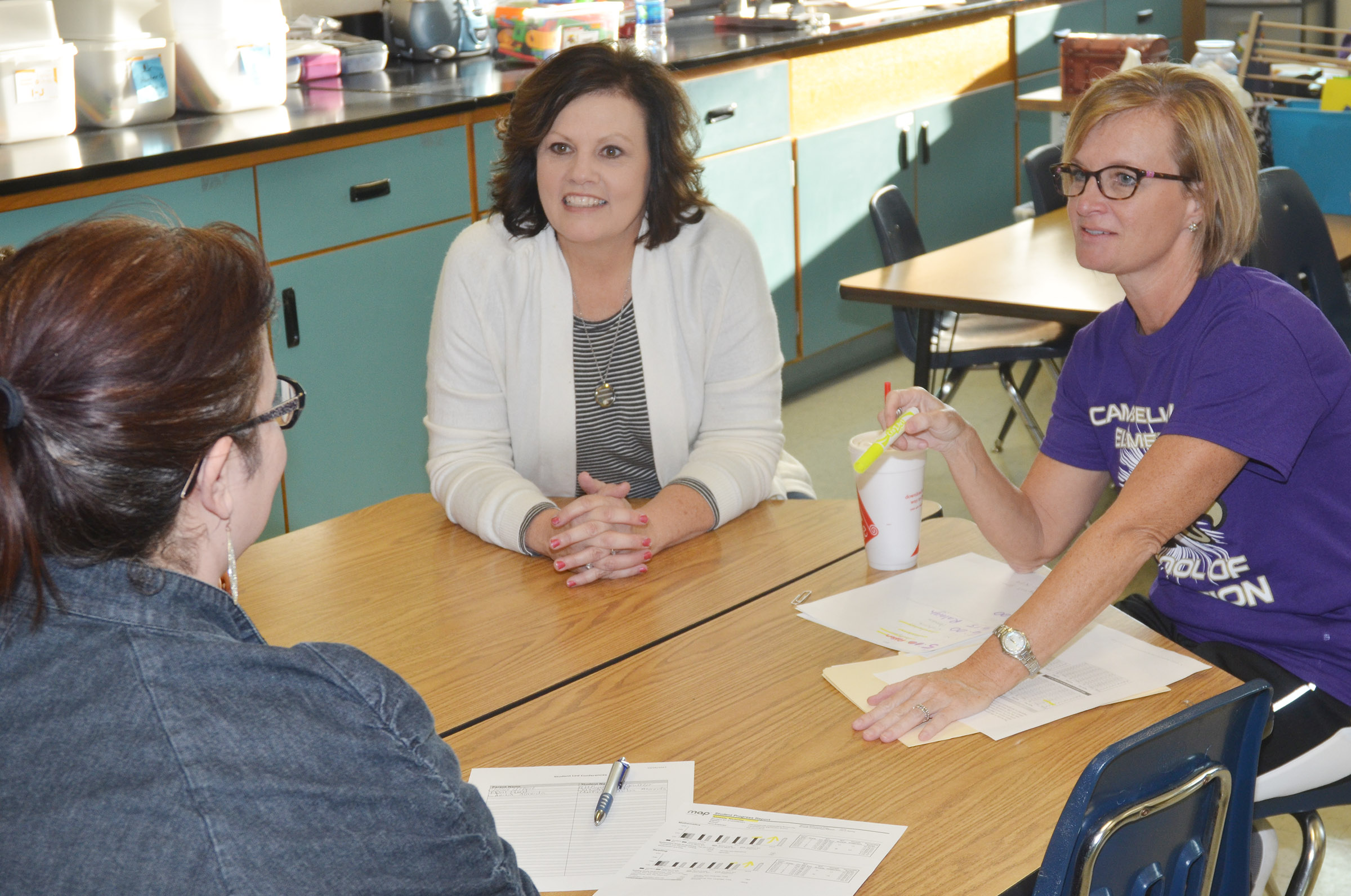 Former CES second-grade teacher Melanie Cox, at right, and Lisa Kearney, who is now teaching Cox's class, talk with a parent.