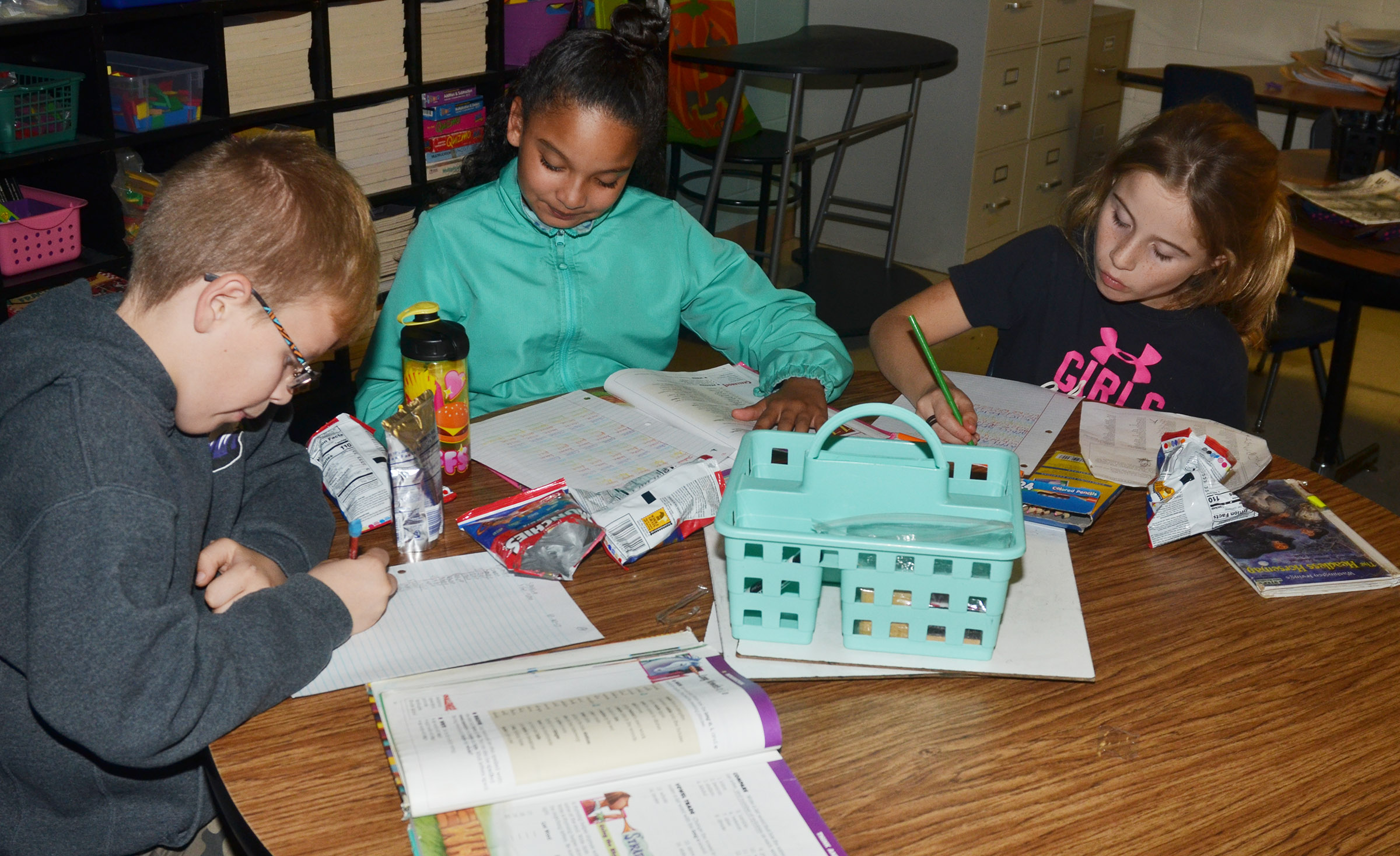 From left, CES fourth-graders Ethan Irwin, Aleecia Knezevic and Reagan Hayes work on their homework and write their spelling words.