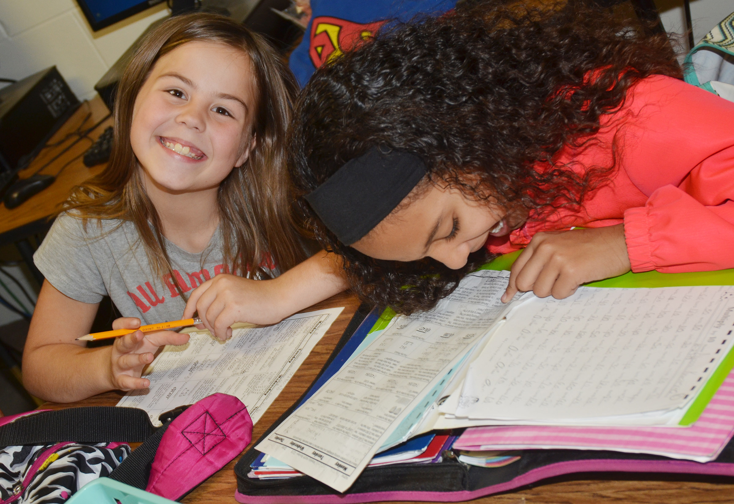 CES fourth-graders Chloe Bates, at left, and Alyssa Knezevic work on their homework.