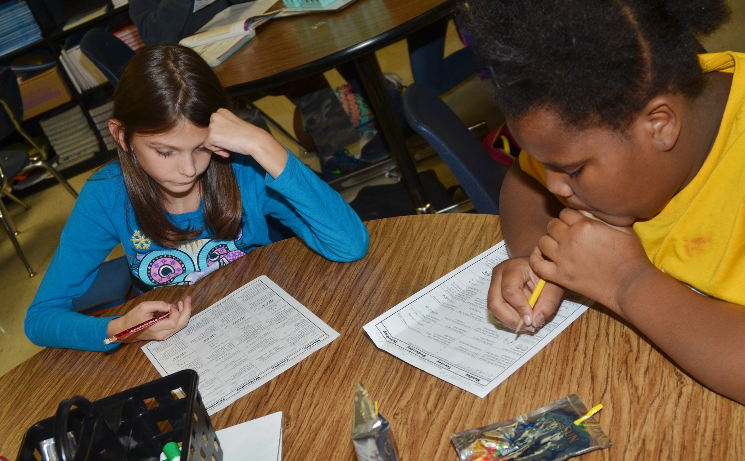 CES fourth-graders Madie Gebler, at left, and Talaysia Daniels work on their homework.