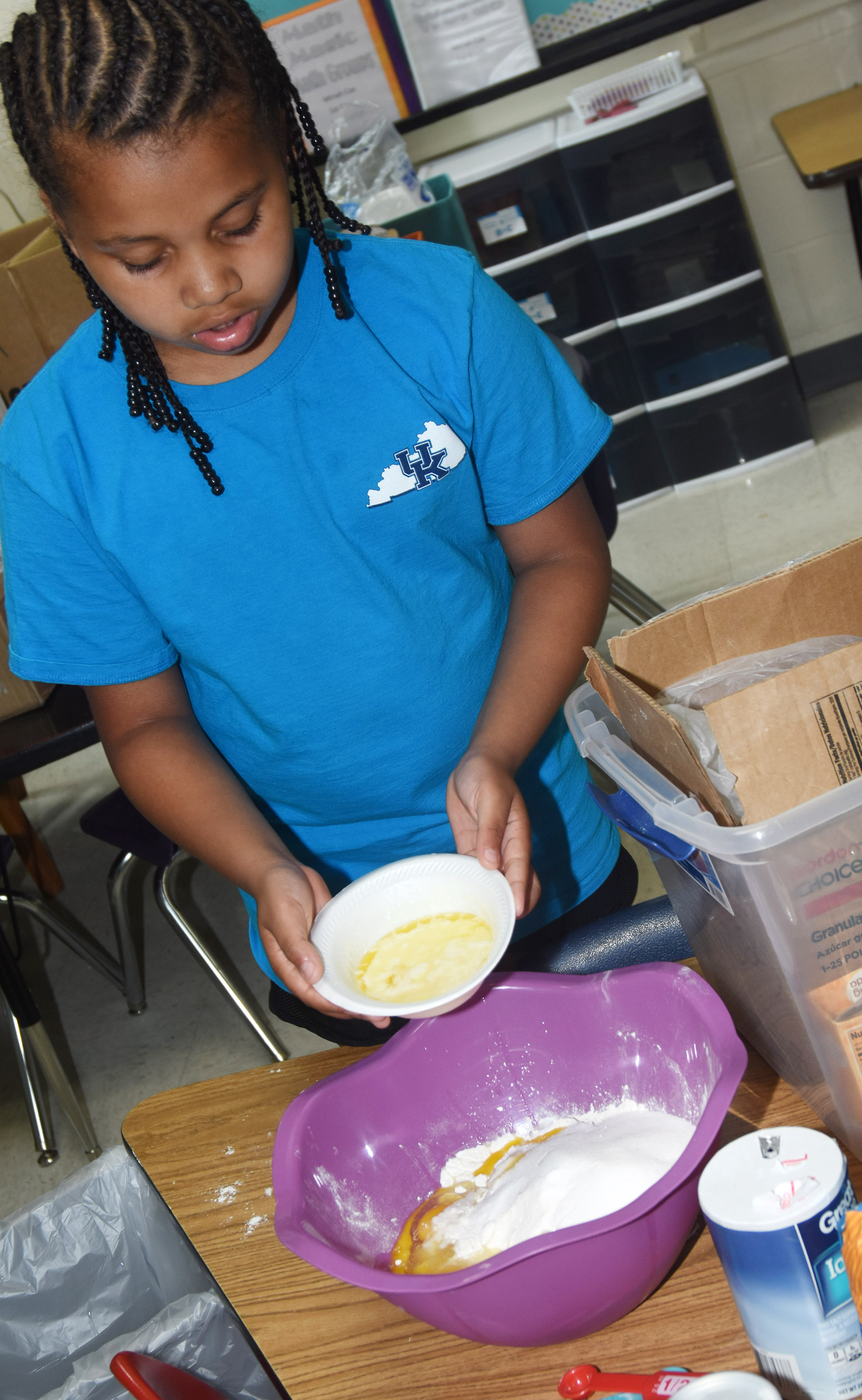 CES second-grader Journey Webb mixes ingredients to make homemade muffins.